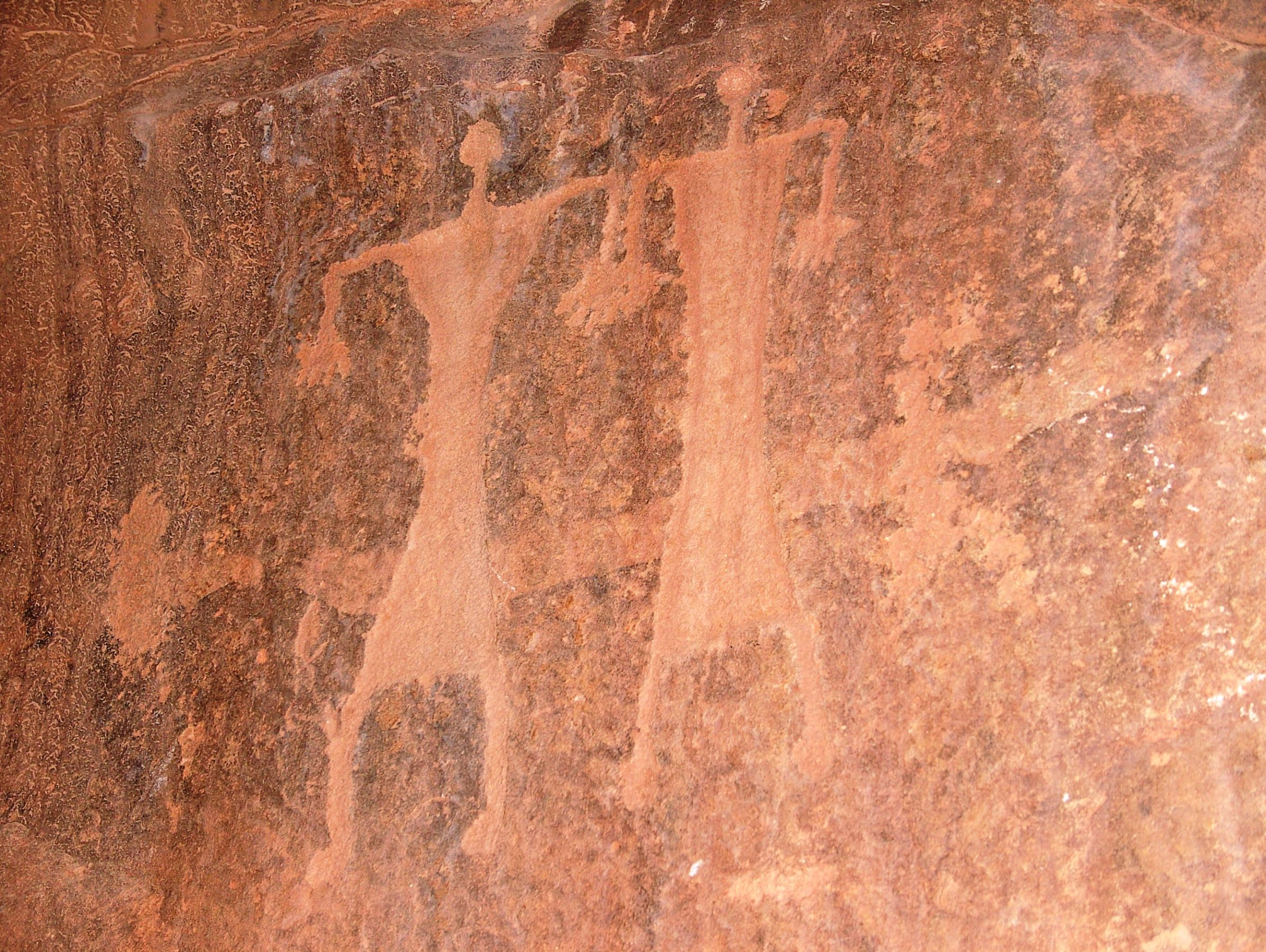 Close-up of a petroglyph of two people carved into a rock wall at Wadi Rum