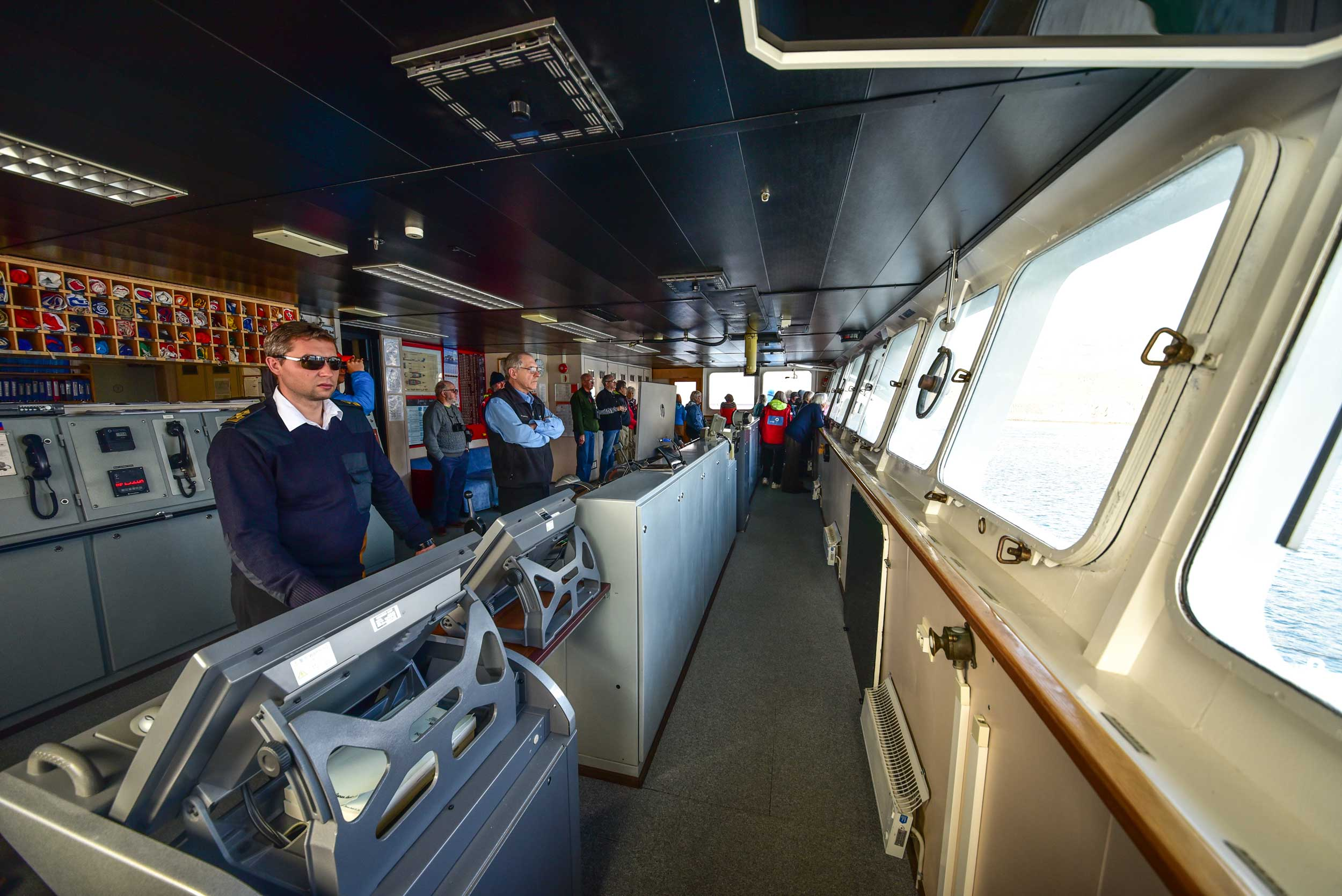 The bridge of a ship with crew at the controls and civilians standing amongst them looking out to sea