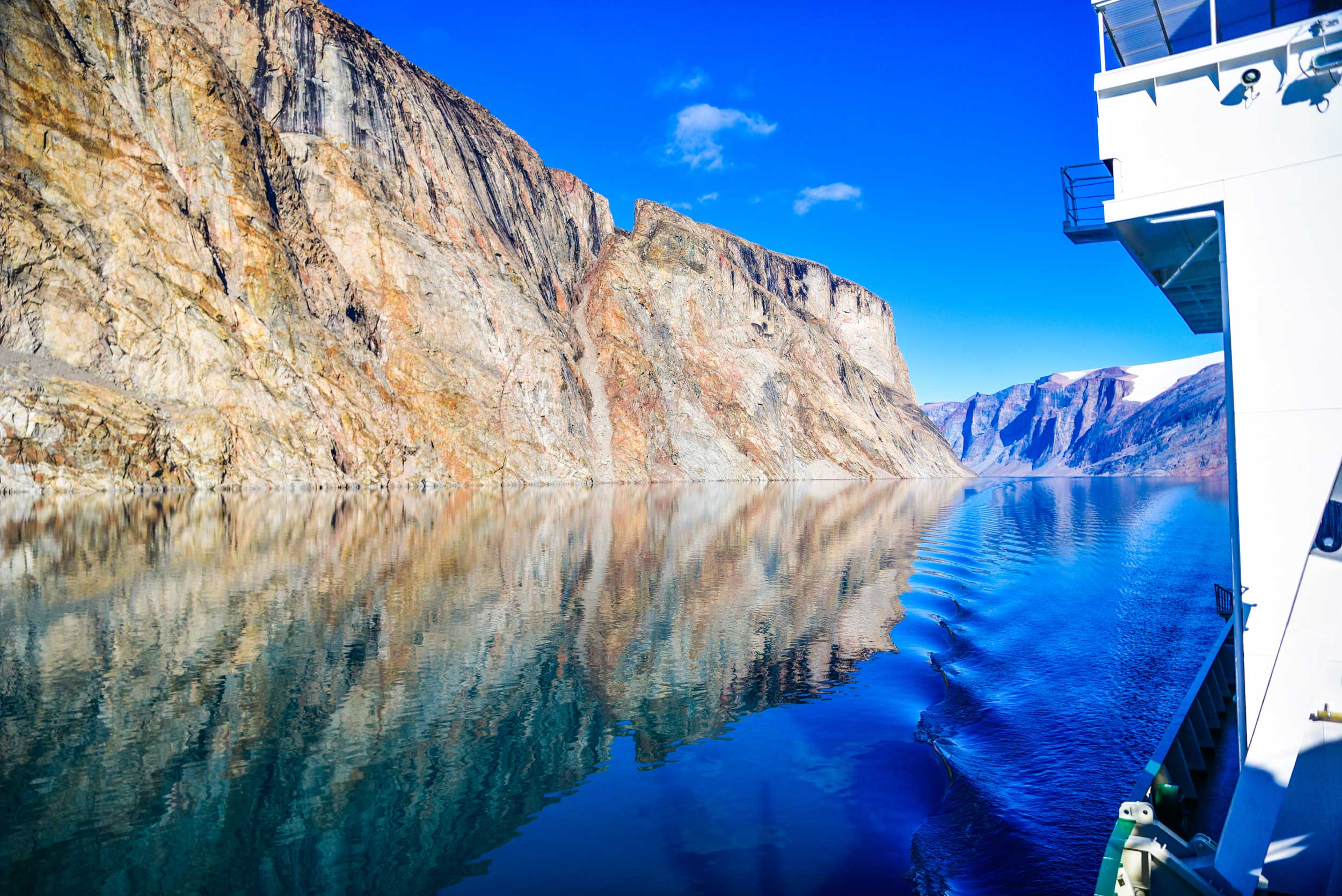 Bright blue water with high brown cliffs either side rflected in the mirror-like water