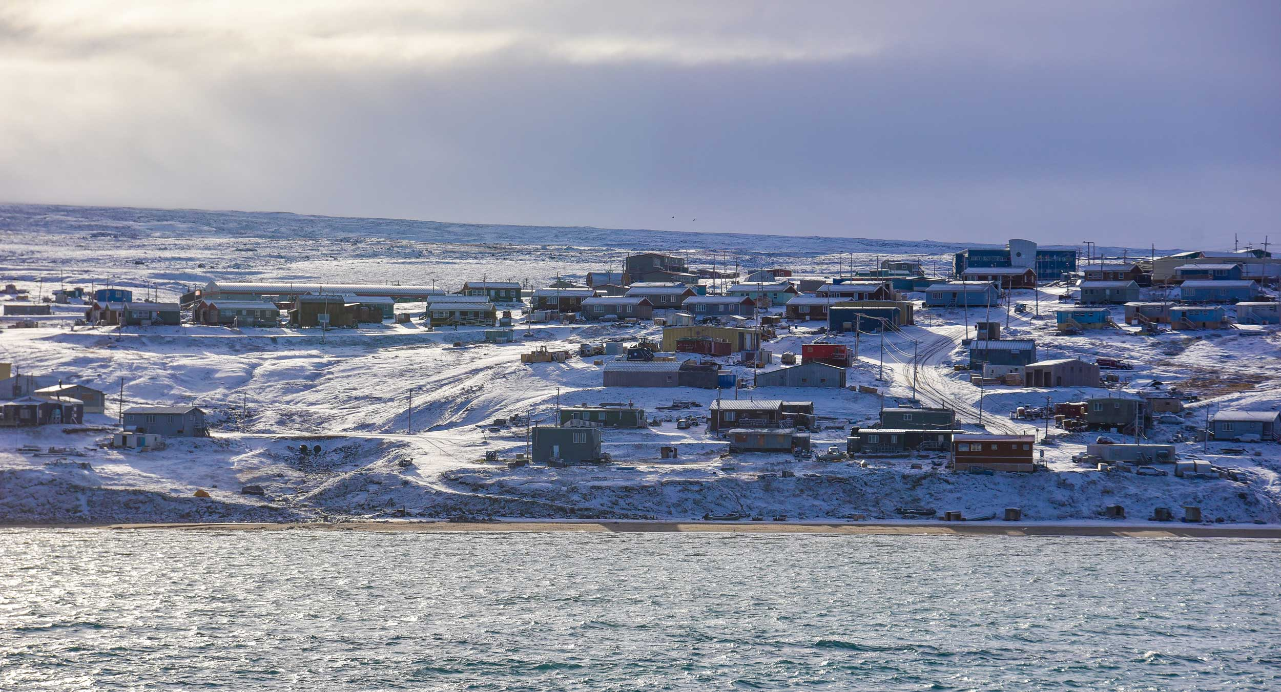 A cluster of shacks on a snowy hill by the sea