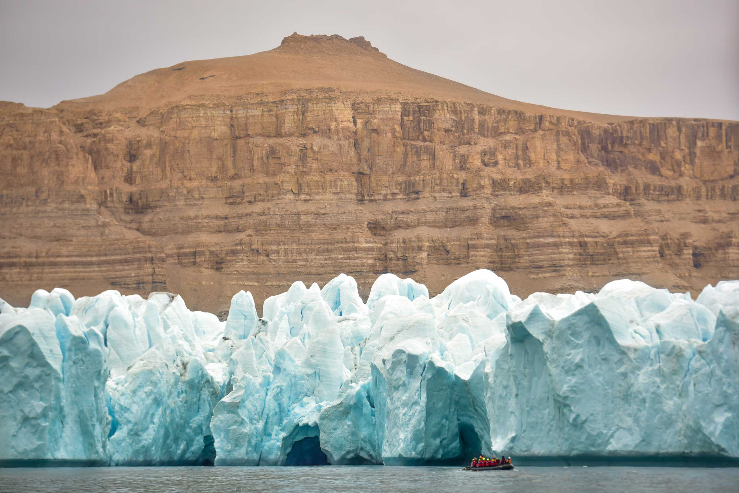 Large brown mountain with blue-white glacier in front of it