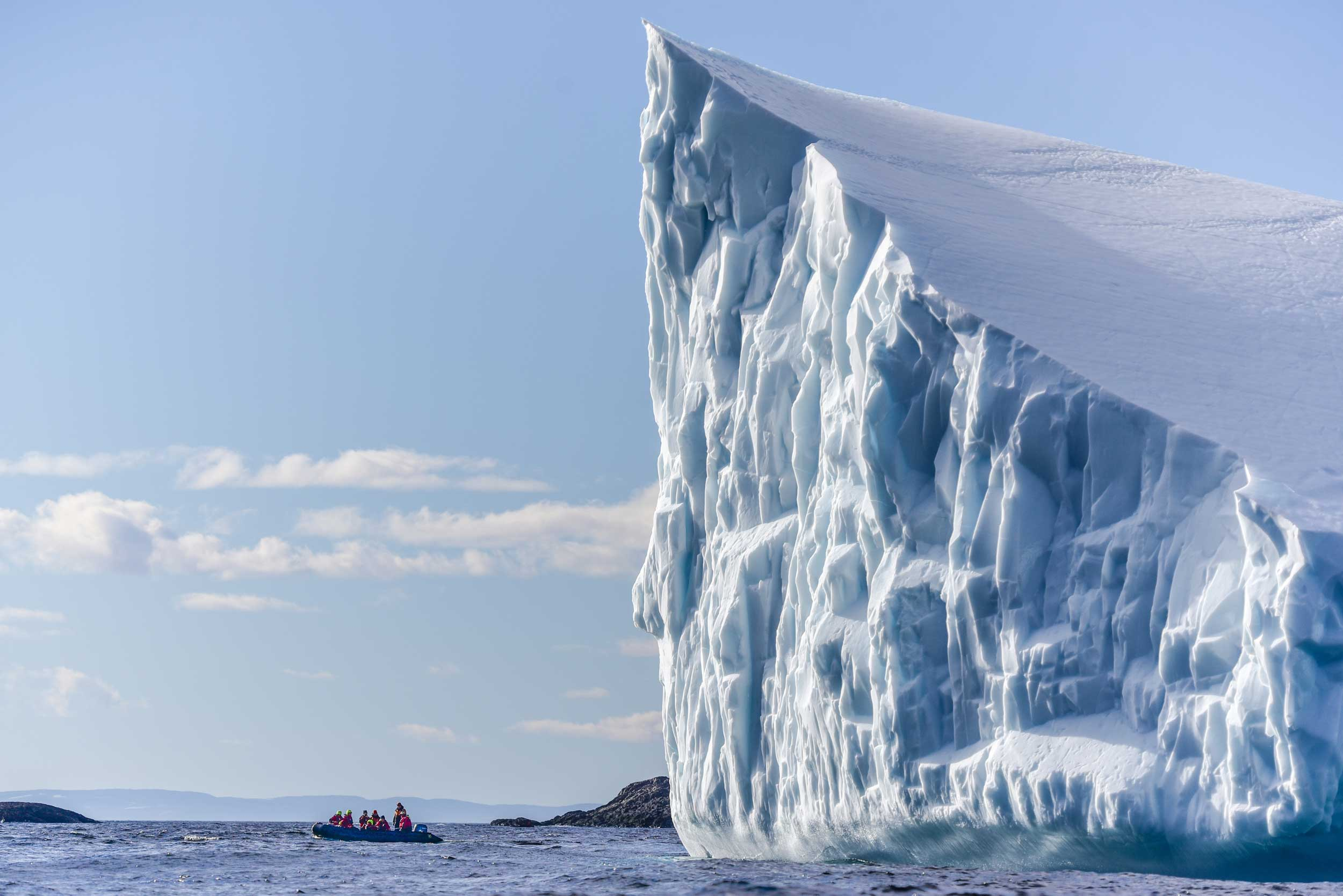 Huge pointed iceberg with small zodiac boat and passengers to the left