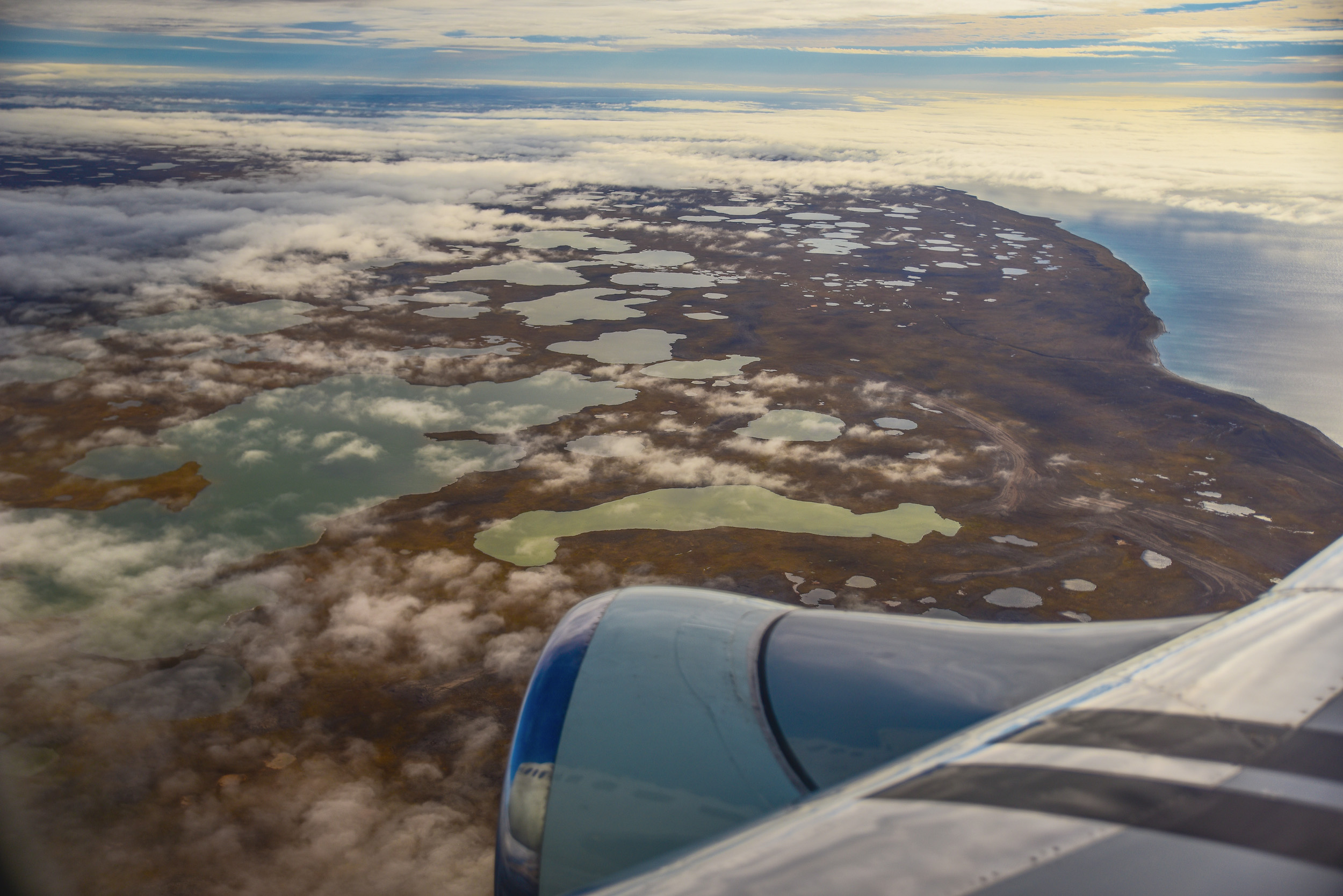 View of an aircraft engine and islands seen through scattered clouds out of an aircraft window