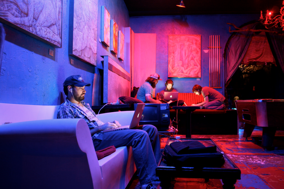 Pink and purple lounge with man sitting on a sofa using a laptop and headphones with others in the background on couches working away on their laptops, LA