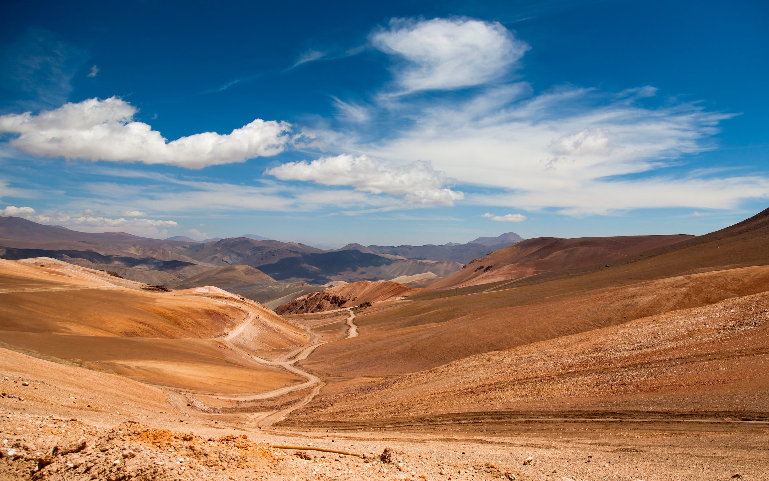 A zig-zag dusty road cutting through the dry, brown hills of the Atacama Desert