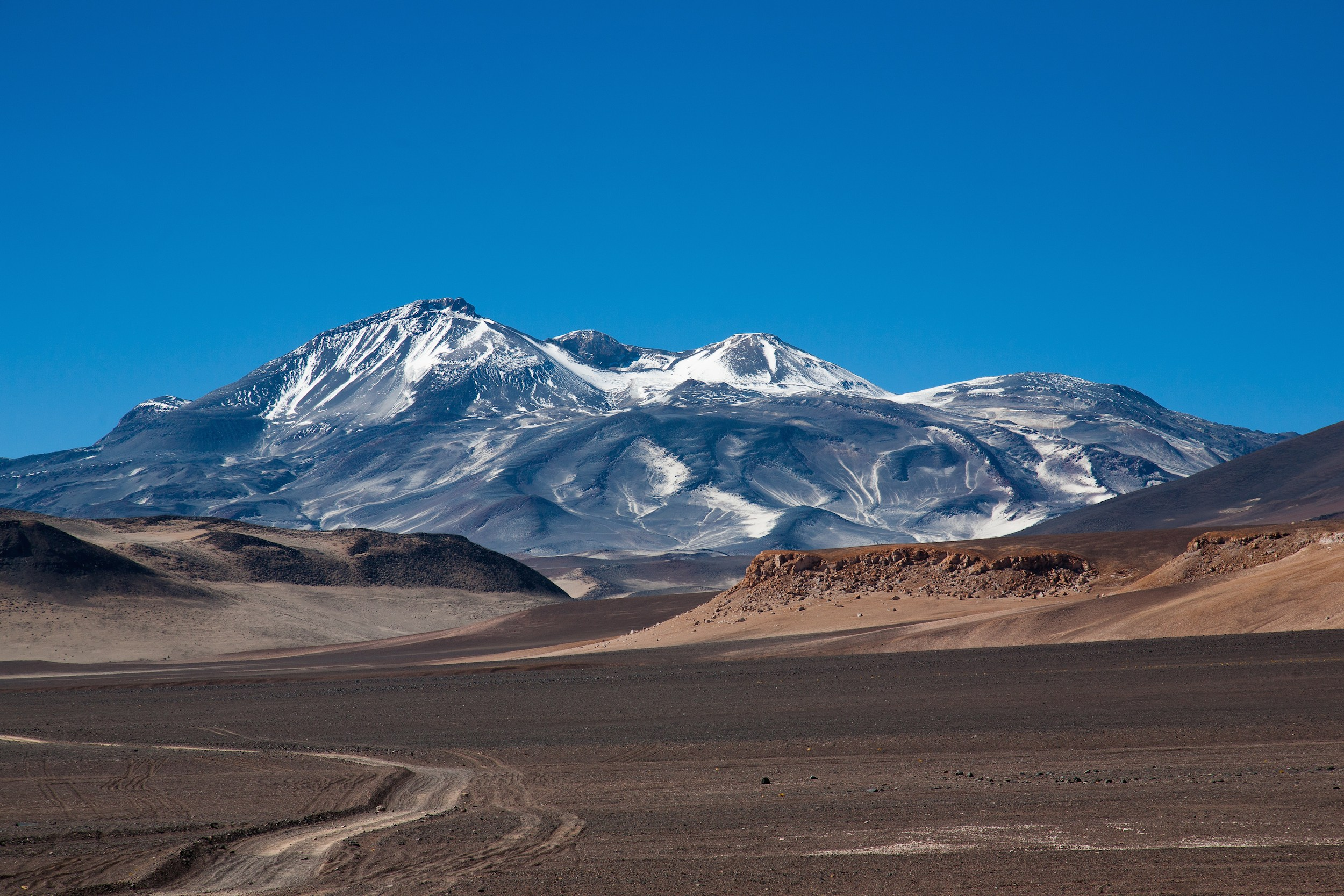 The snow-dusted volcanic peaks of Ojos del Salado, Atacama. Photo by Brigitte Djajasasmita