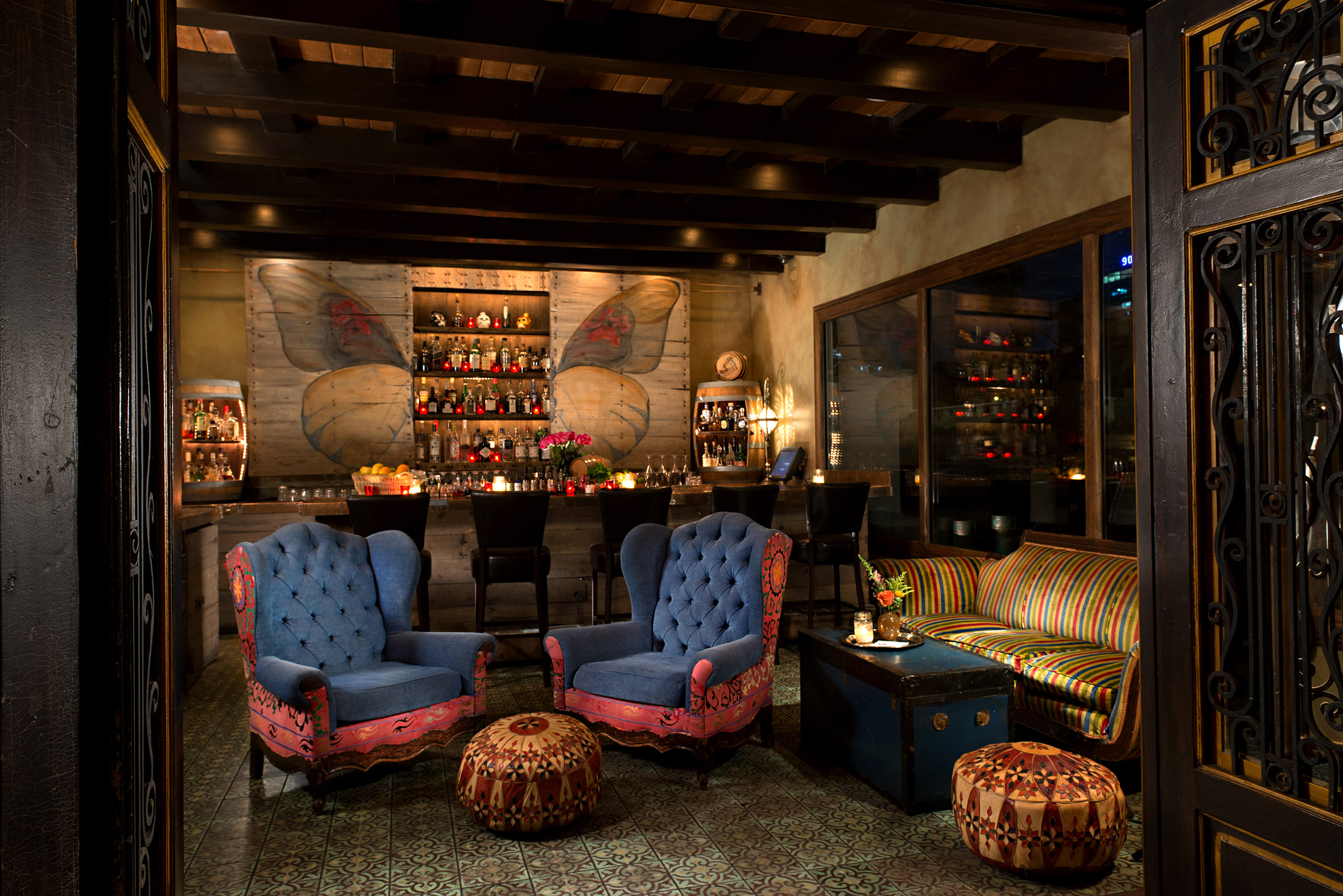 Dimly lit room with two blue and pink, elegant wingback chairs in front of a bar with butterfly motif on the wall in Los Angeles