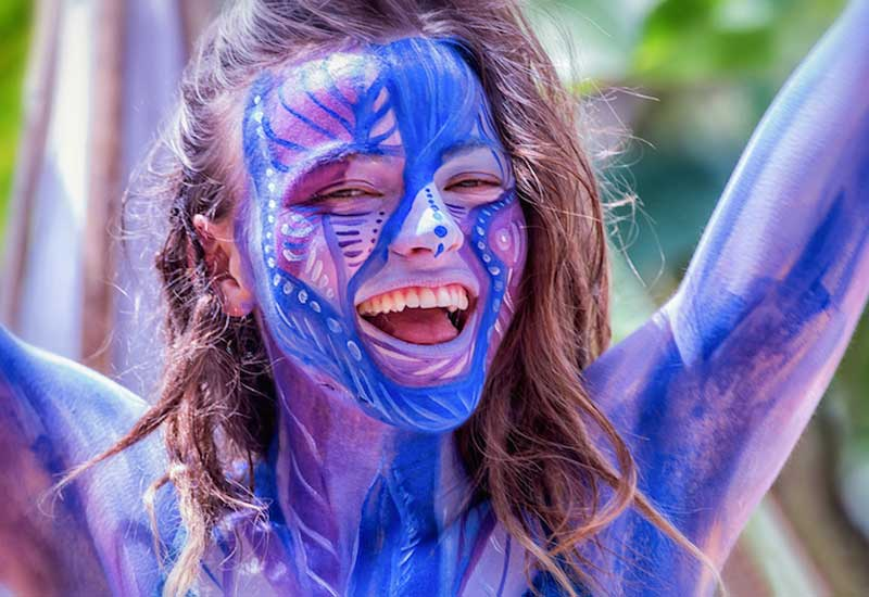 Close-up of girl's laughing face and shoulders covered in a blue body paint design