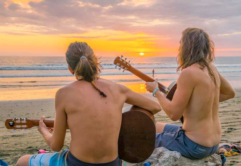 Two men seated on the sands playing their guitars facing a brilliantly lighted sunset sky