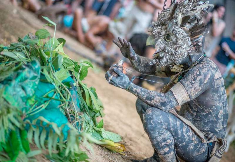 Person dressed as a mud man couched beside a pile of leaves at Envision
