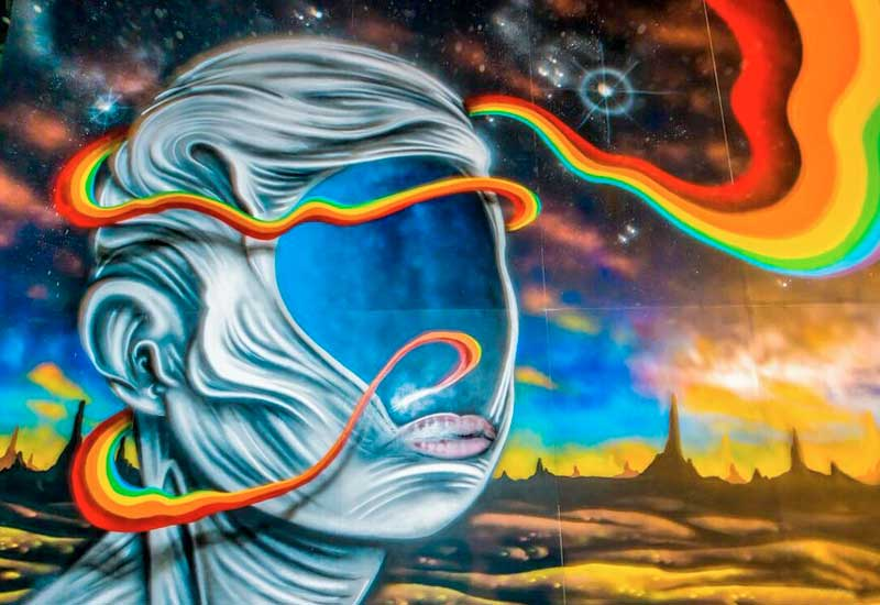 A mural of a faceless head and a rainbow twirling through it and around the head, Costa Rica
