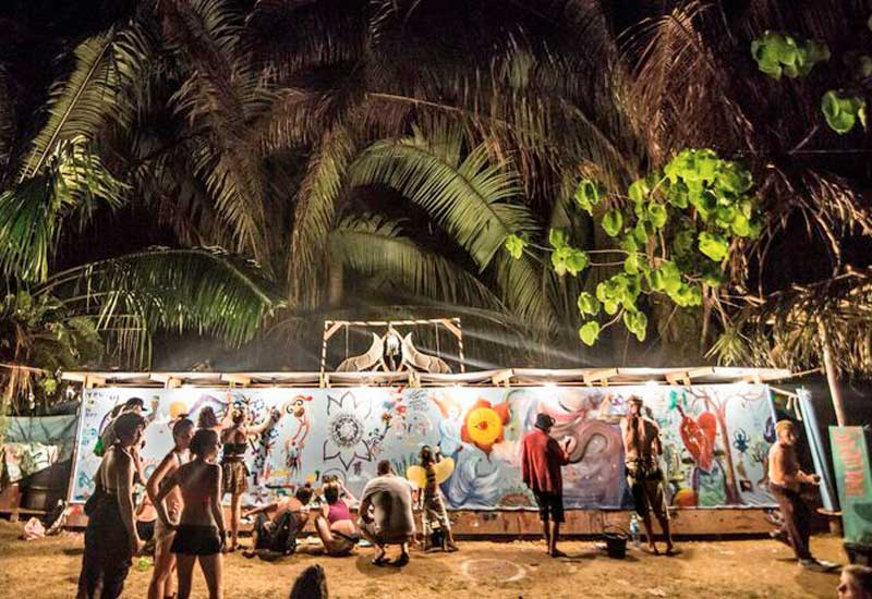 People painting murals on a long wall at night