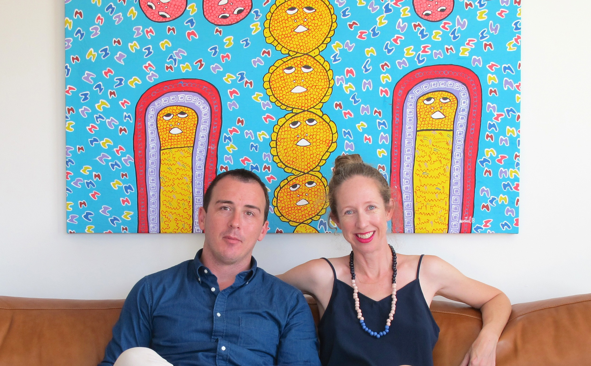 Man and woman sitting in front of large, brightly coloured Haitian painting