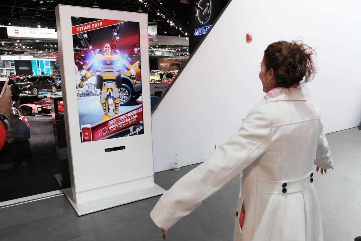 A girl smiling at her image on a screen in costume at NAIAS