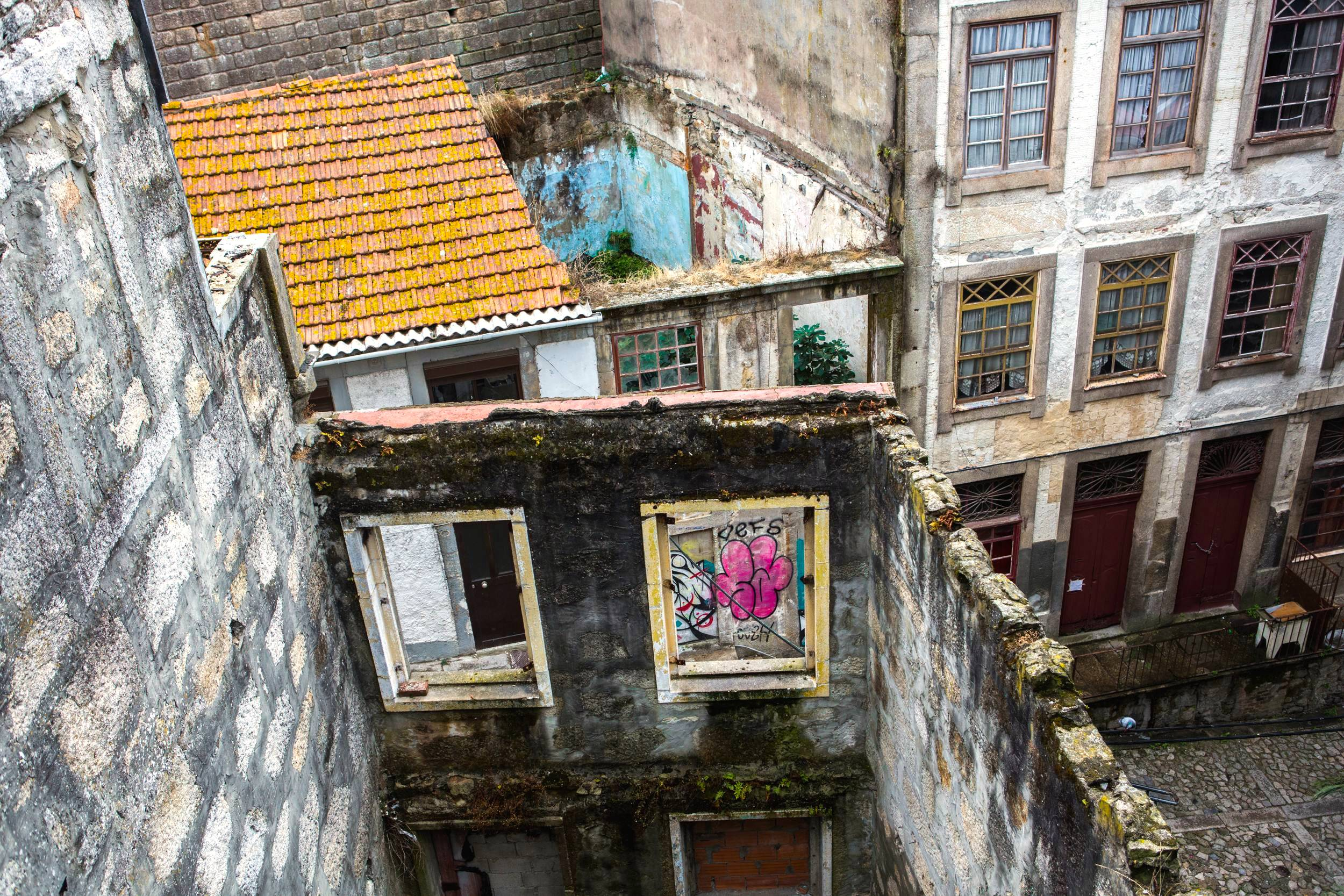 Looking down at building facades with nothing behind them and the cobblestoned street, Porto, Portugal