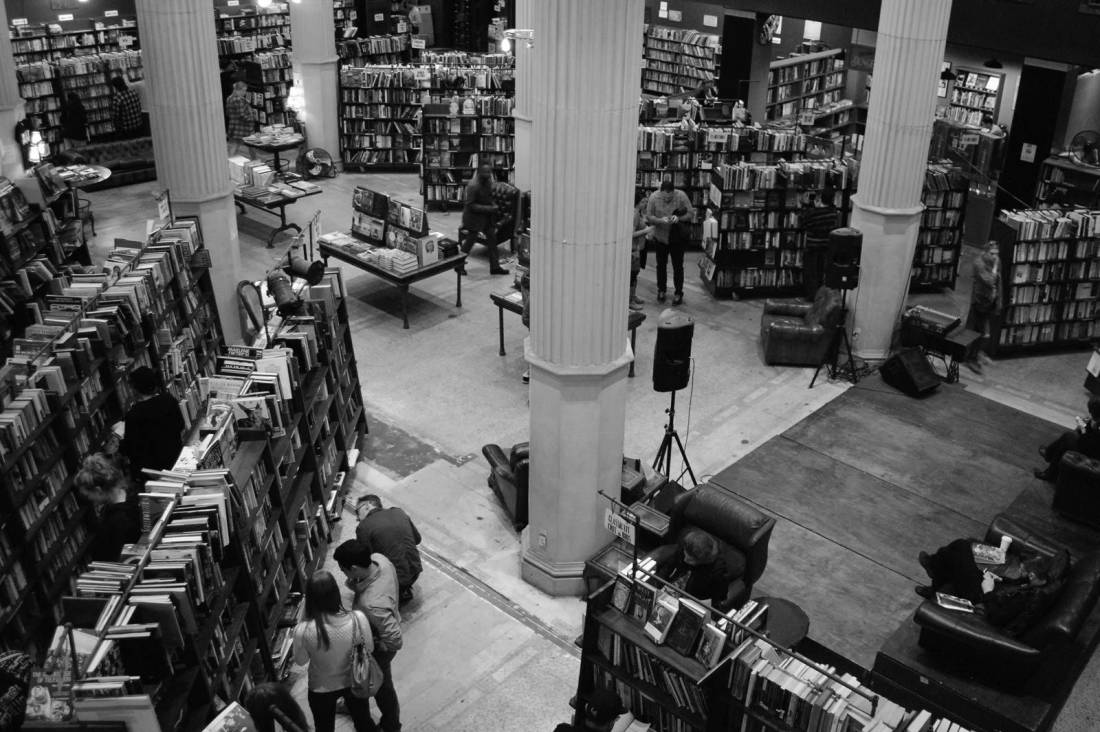 Black and white image of rows of books on bookshelves in a high-ceilinged room with Doric columns and customers browsing through them