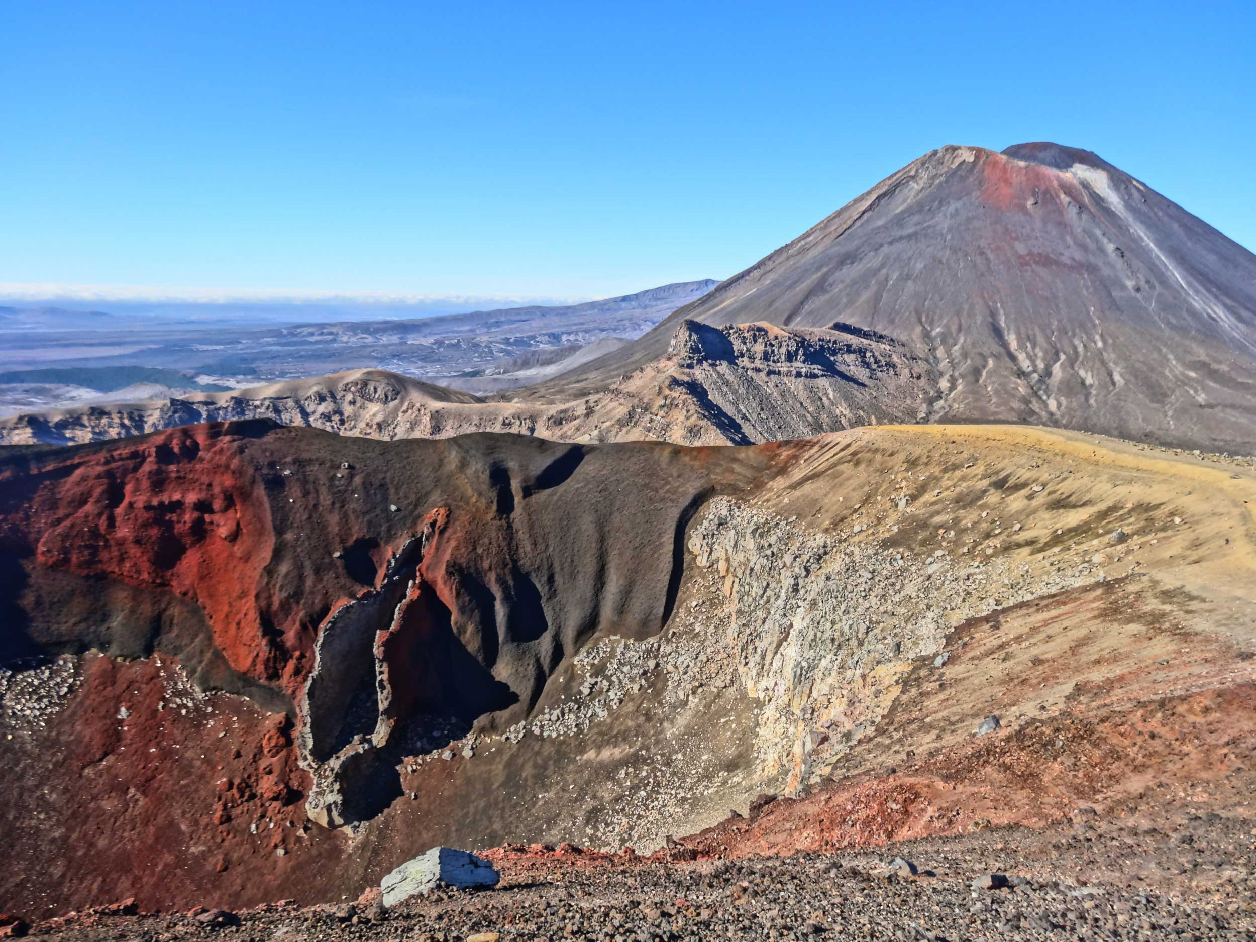 A deeply scarred volcanic crater with varying shades of red, brown and black magma with another conical volcano behind it at Tongariro, New Zealand