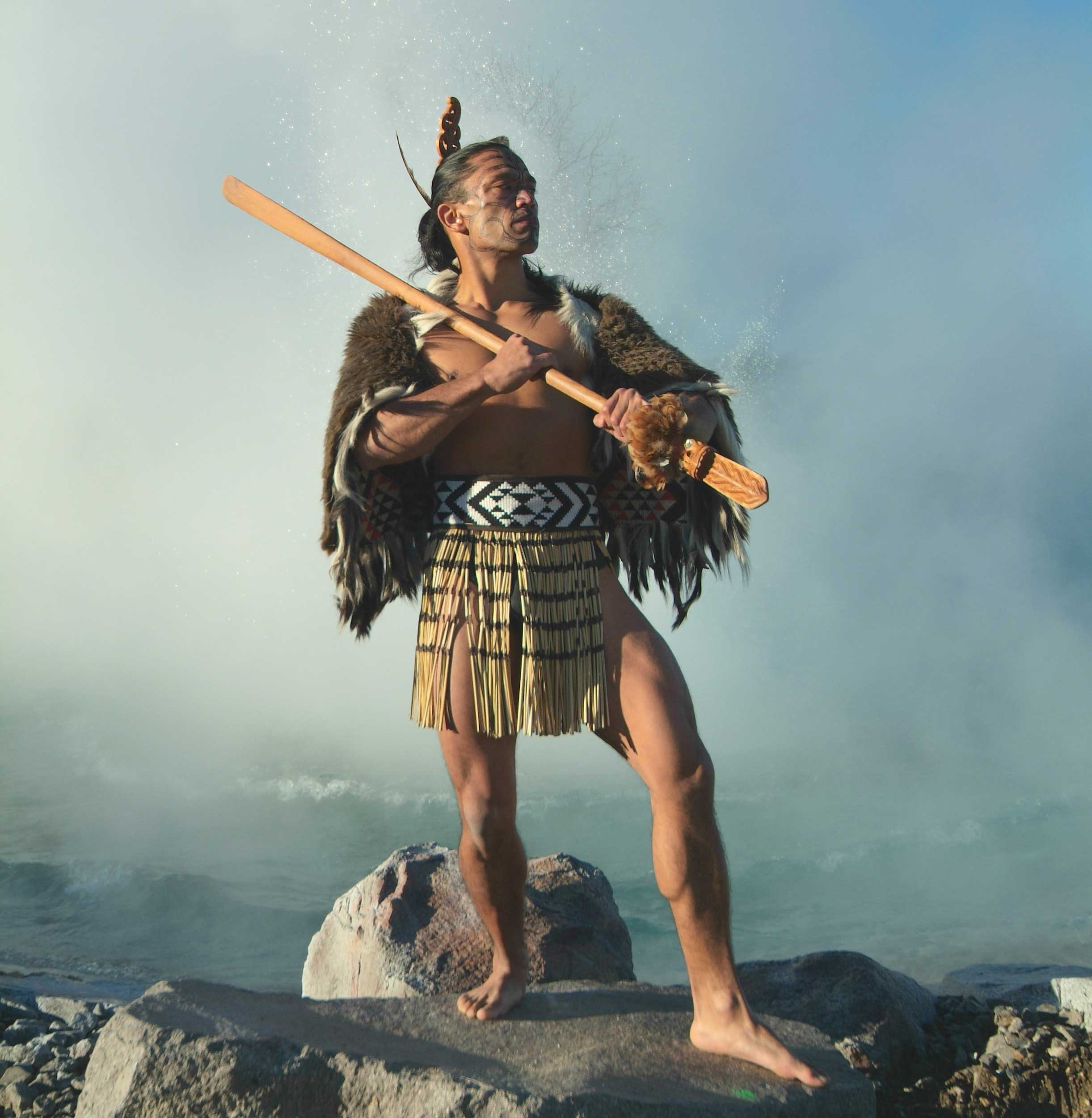 A man dressed in a cloak of feathers and a loin cloth holding a long club resting on his shoulder, New Zealand