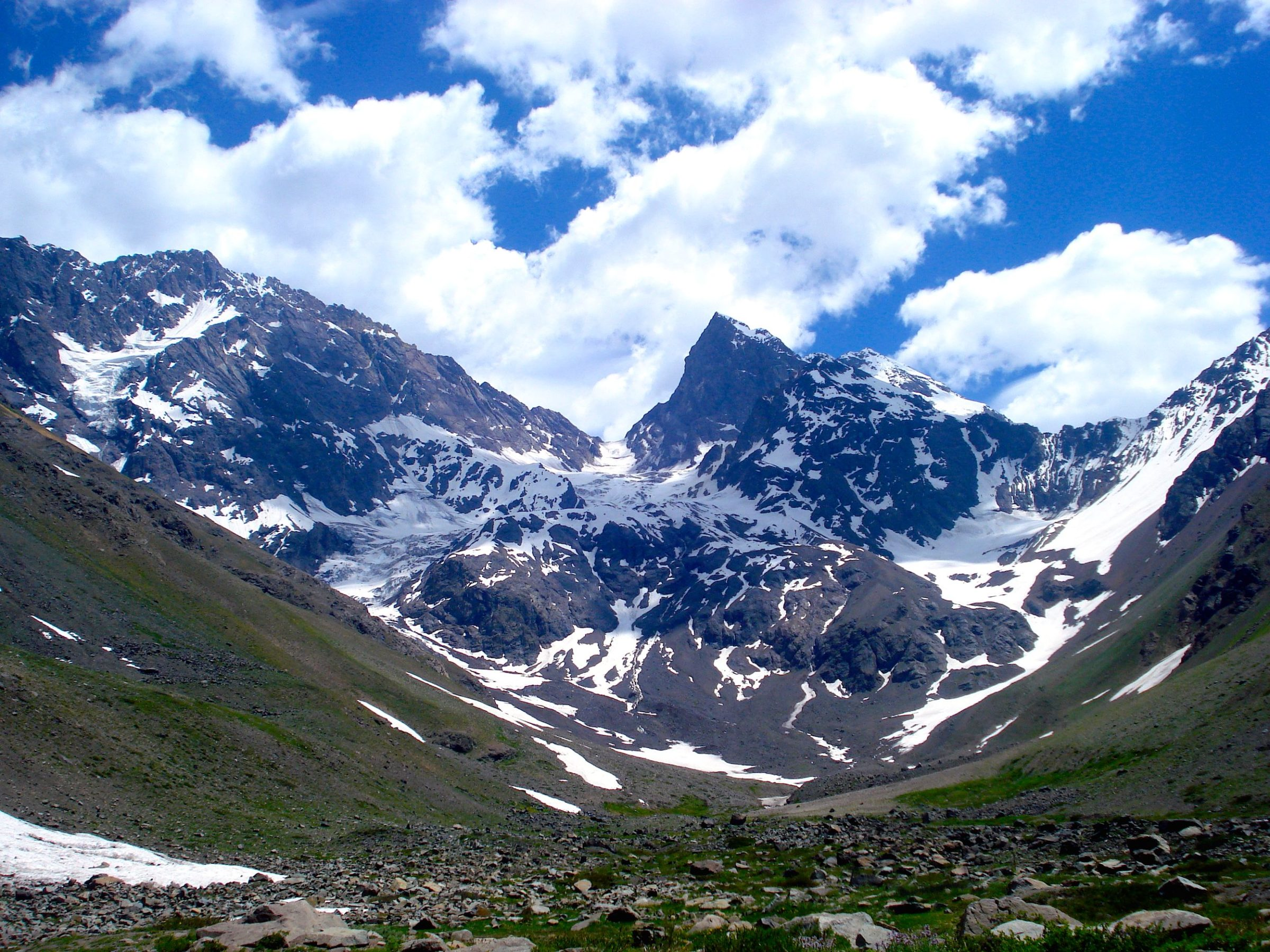 Valley with grass in the foreground and snow-capped mountains in the background