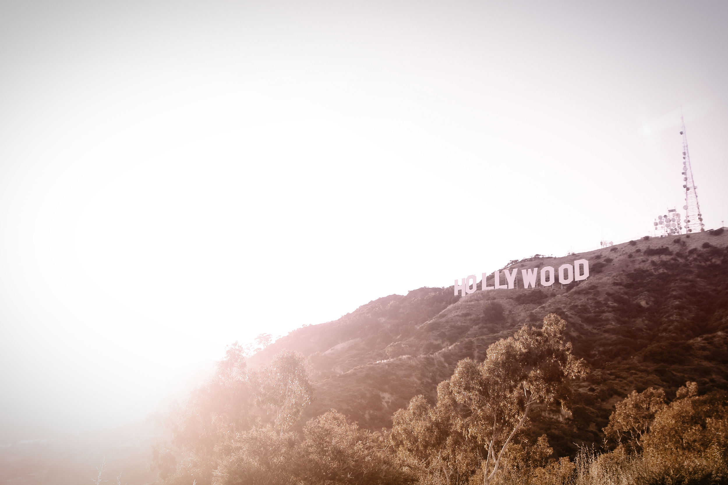A misty shot of the Hollywood sign on the hillside with a pylon on the crest