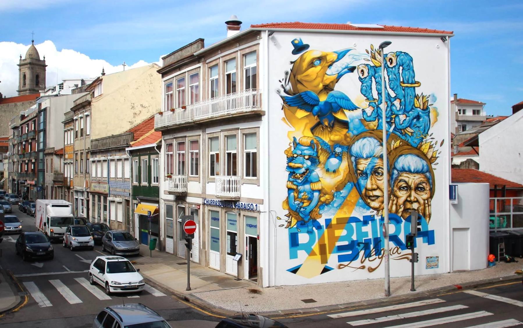 A huge blue and yellow mural covering the entire side of a two storied building in Porto