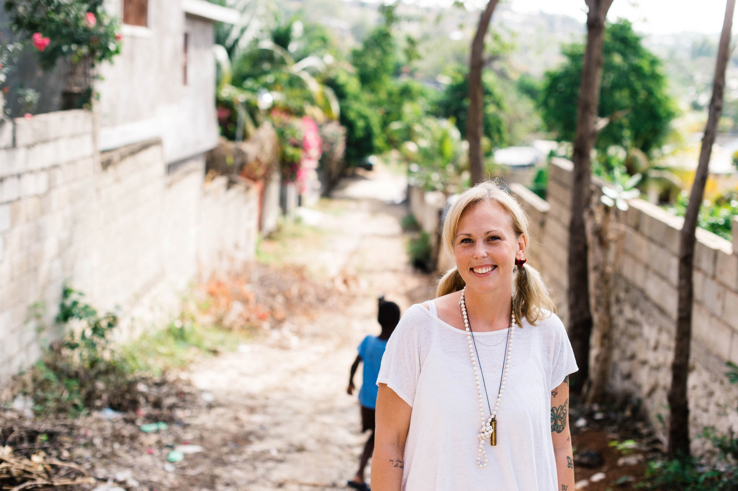 ,Blonde-haired smiling lady in a white top photographed outdoors in Haiti