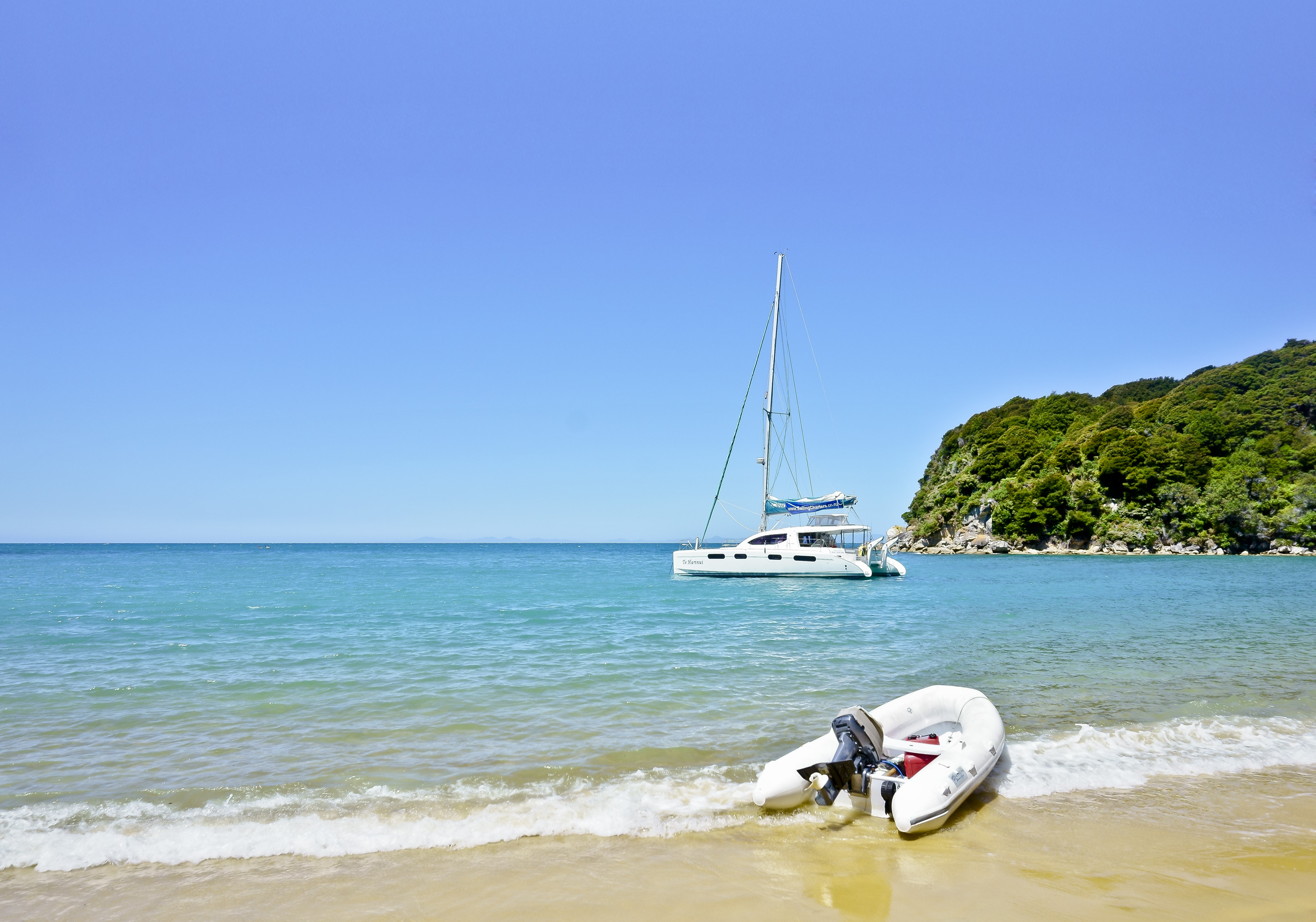 A motorised dinghy at shore and a boat moored further out in the peaceful waters of a bay