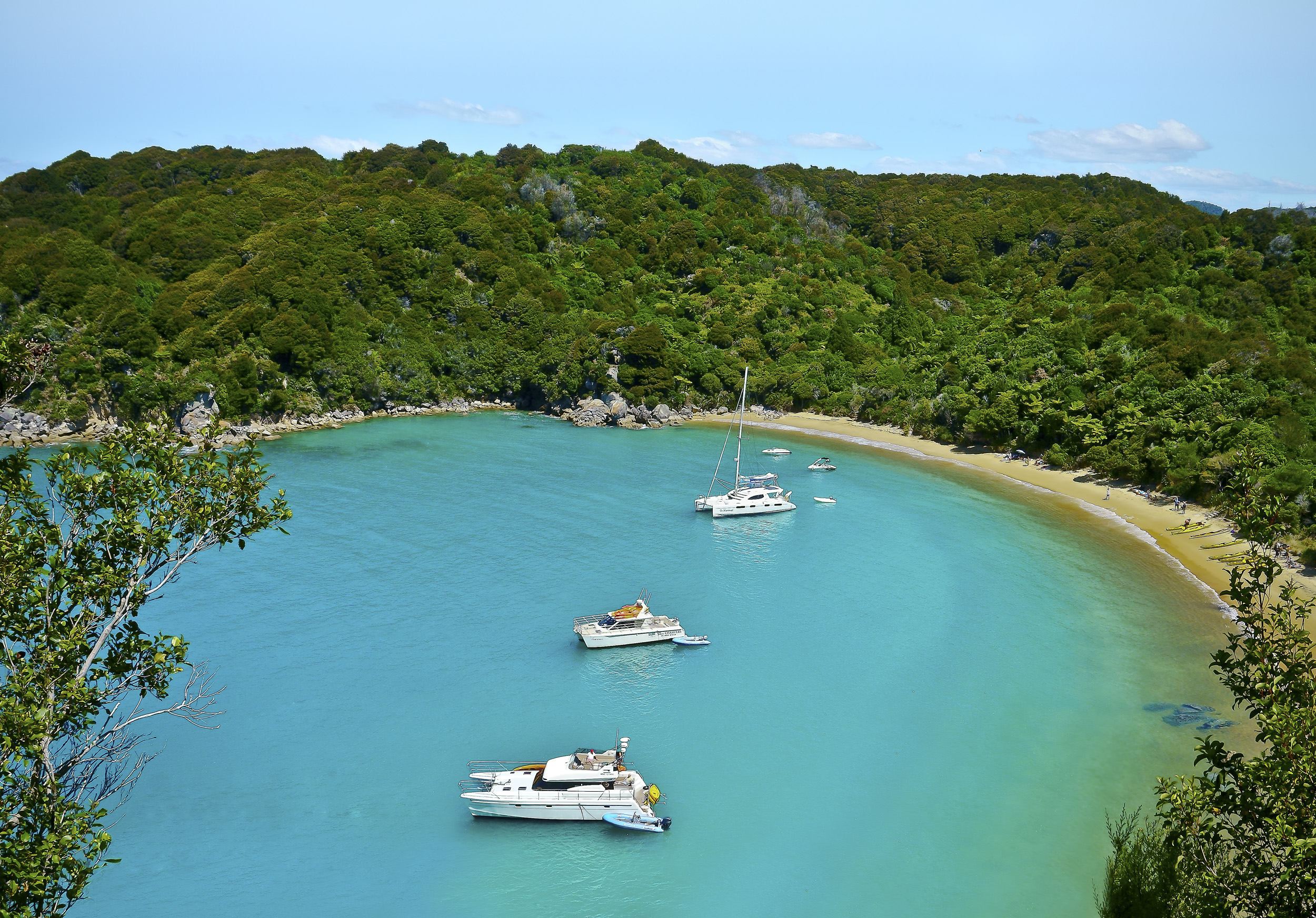 Looking down onto a circular bay with turquoise waters and three moored boats and bush right down to the beach at Abel Tasman