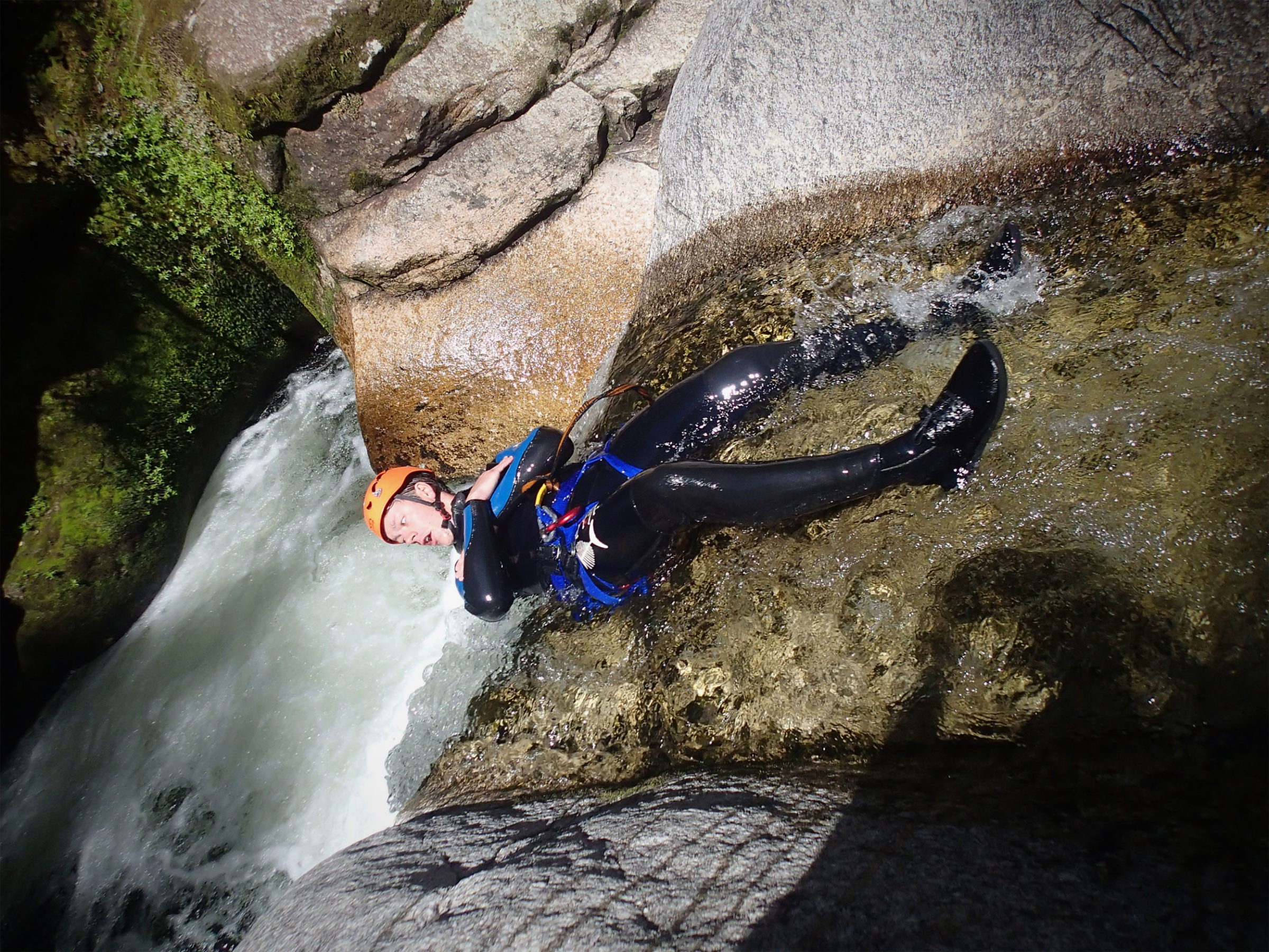 Canyoneer lying on a slab of rock, arms crossed over chest sliding backwards into churning waters below