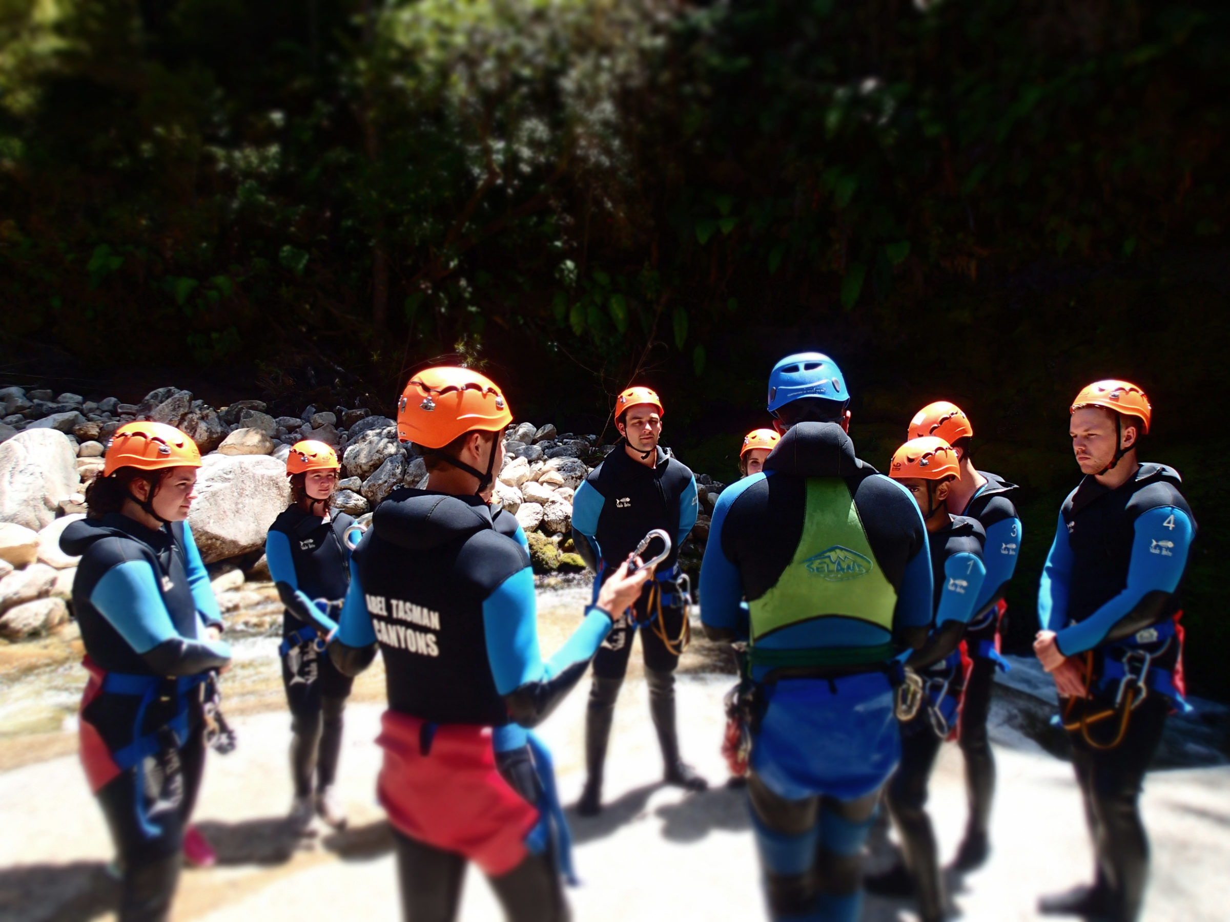A group of canyoneers on a rock standing in a semi-circle around two guides giving a briefing at Abel Tasman National Park