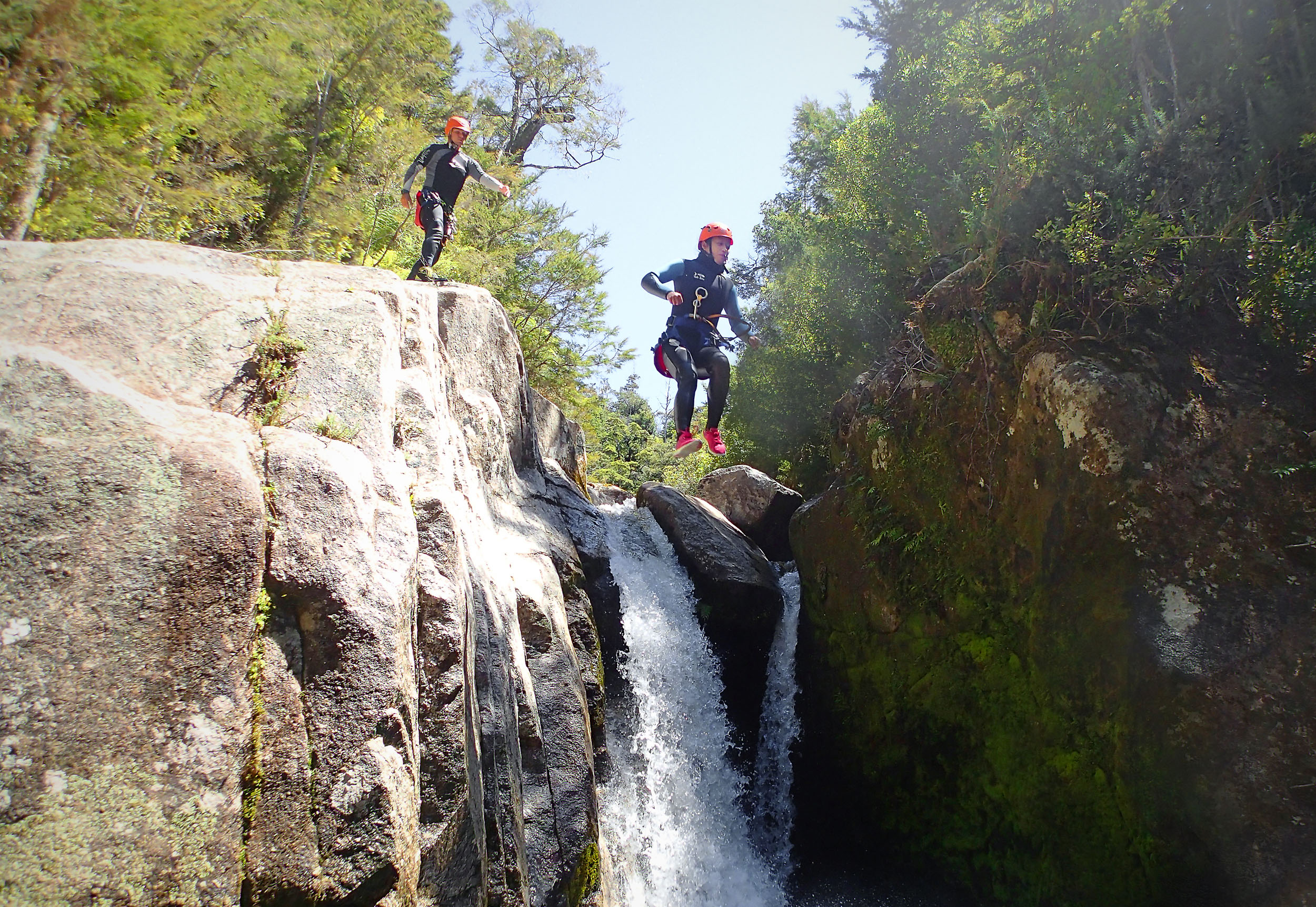 Two canyoneers jumping off a rock by a waterfall, one mid air and the other about to jump at Abel Tasman National Park, New Zealand