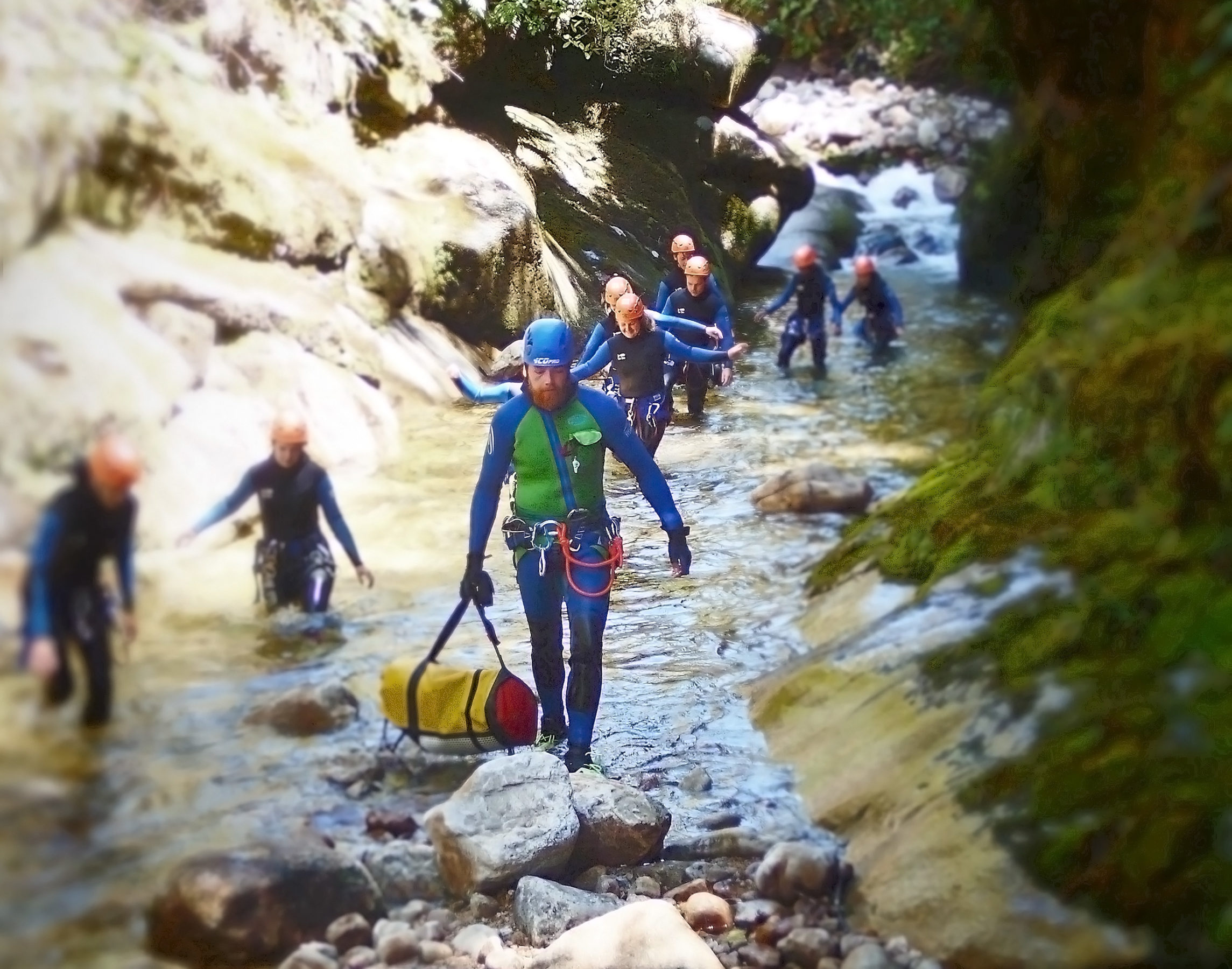 Canyoneer with a bag wading through a stream in a gorge leading a group at the Abel Tasman National Park