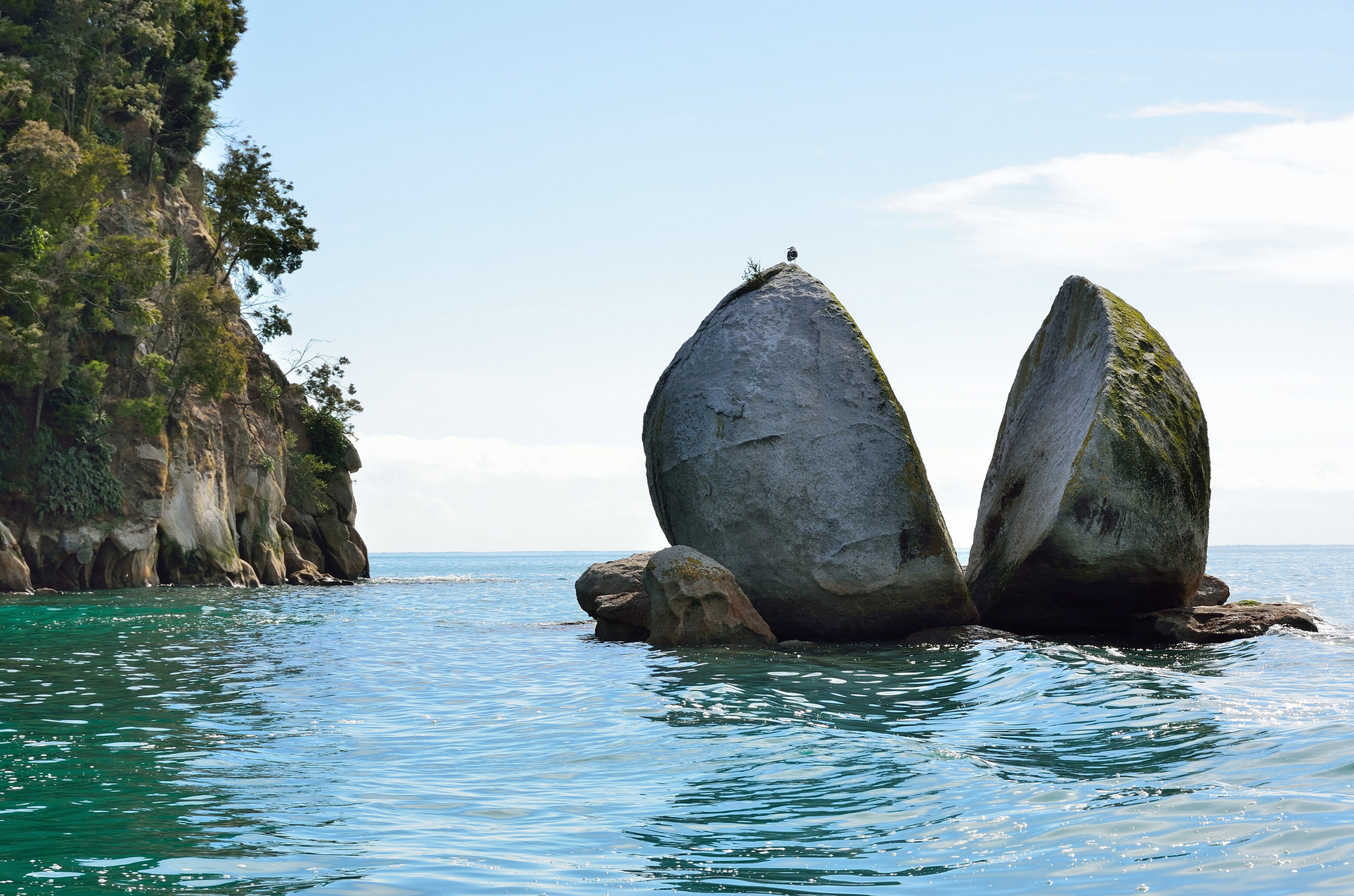 A spherical rock sheared in half an suspended in the waters off Abel Tasman National Park, New Zealand