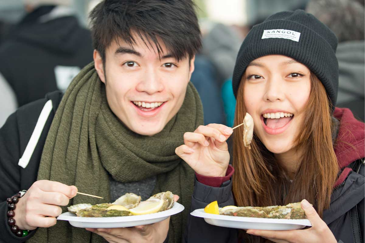 A smiling Asian couple holding plates of oysters and eating them at Bluff Oyster festival