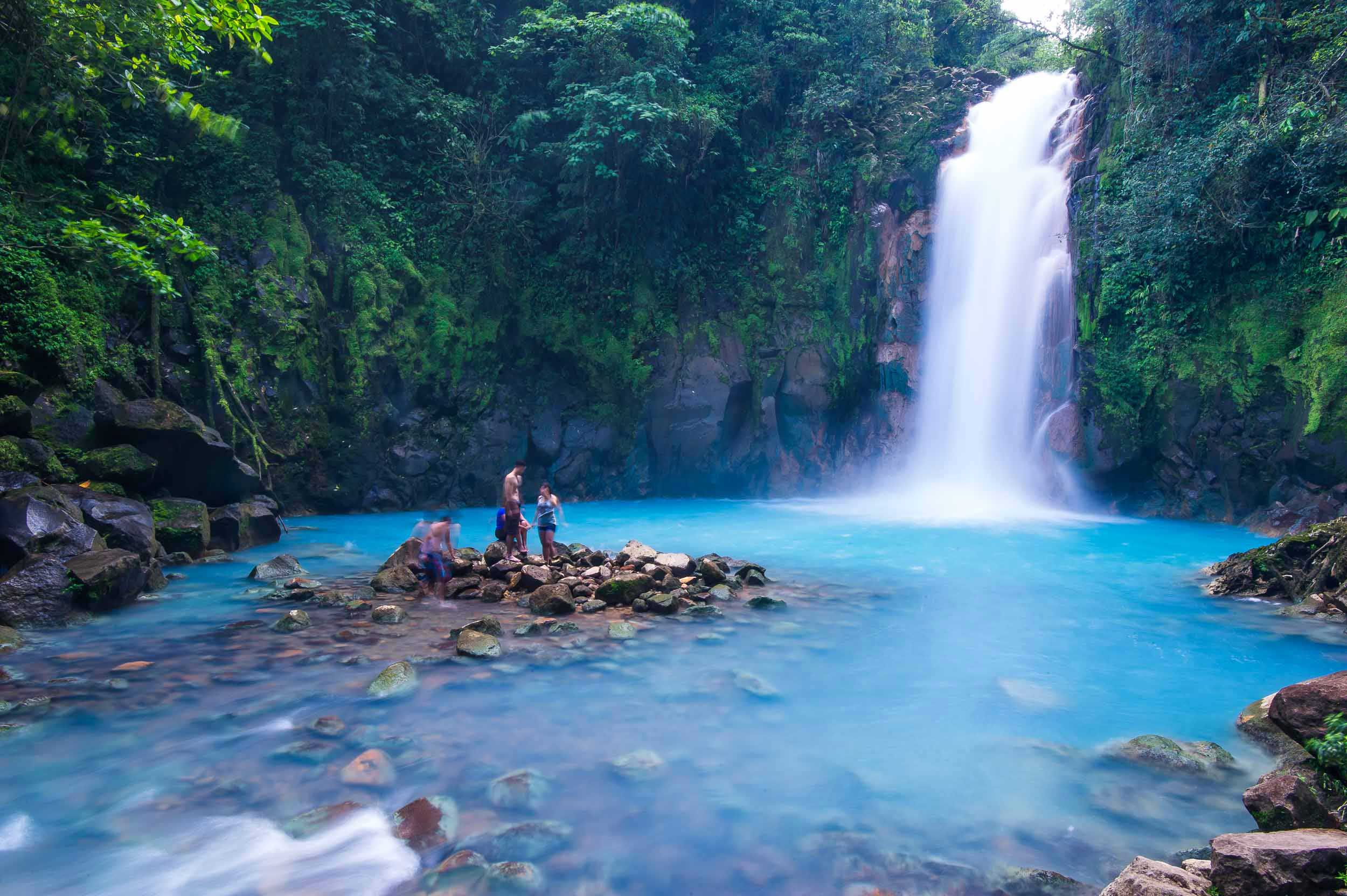 A waterfall cascading into a turquoise blue, rock strewn pool with four people on some rocks, Costa Rica
