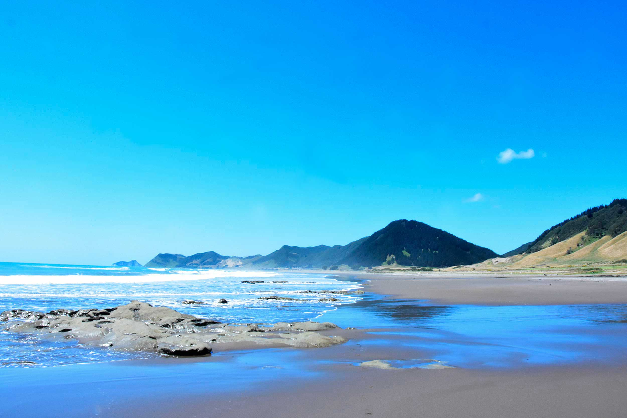A long view of a beach, the sea, rocks in the foreground, a mountain in the distance, East Coast, New Zealand