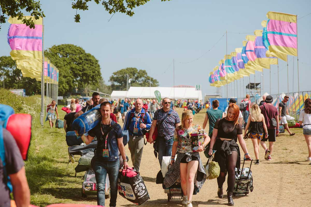 Crowd walking with luggage to campsites at Isle of Wight Festival