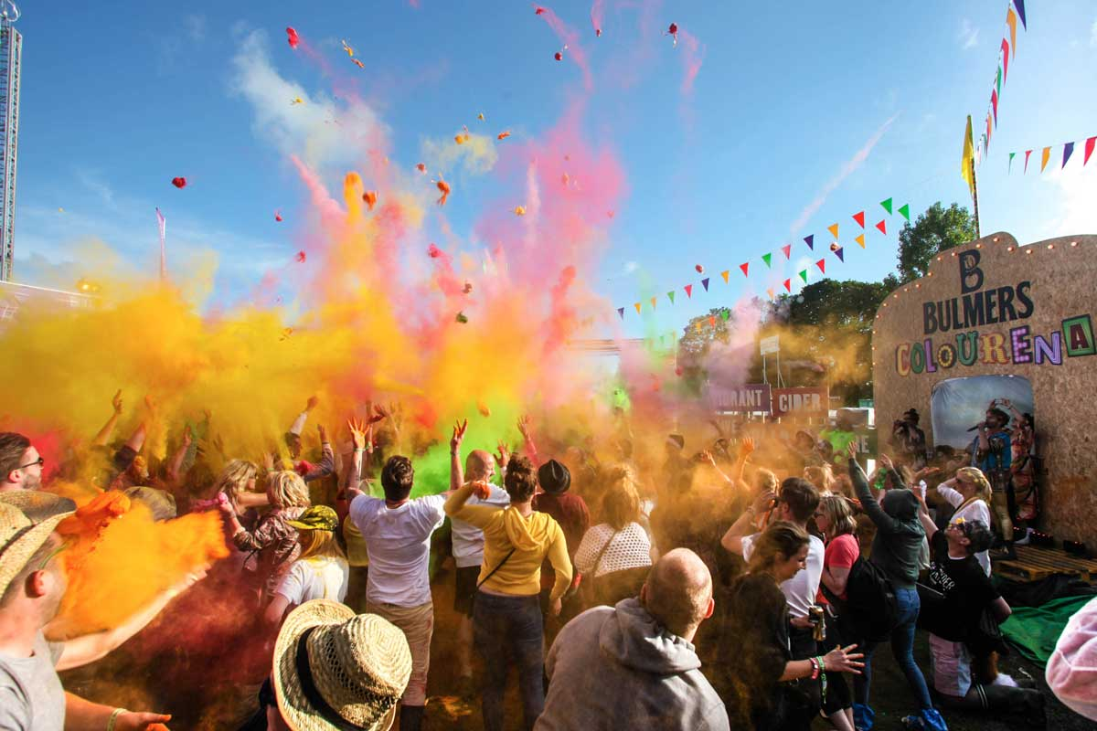 Crowd enjoying throwing coloured powder in the air at the Isle of Wight Festival, UK