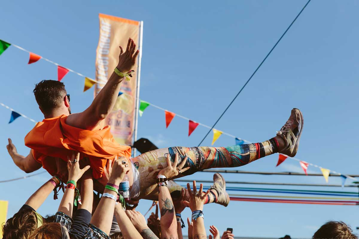 Colourfully dressed man being crowdsurfed, UK