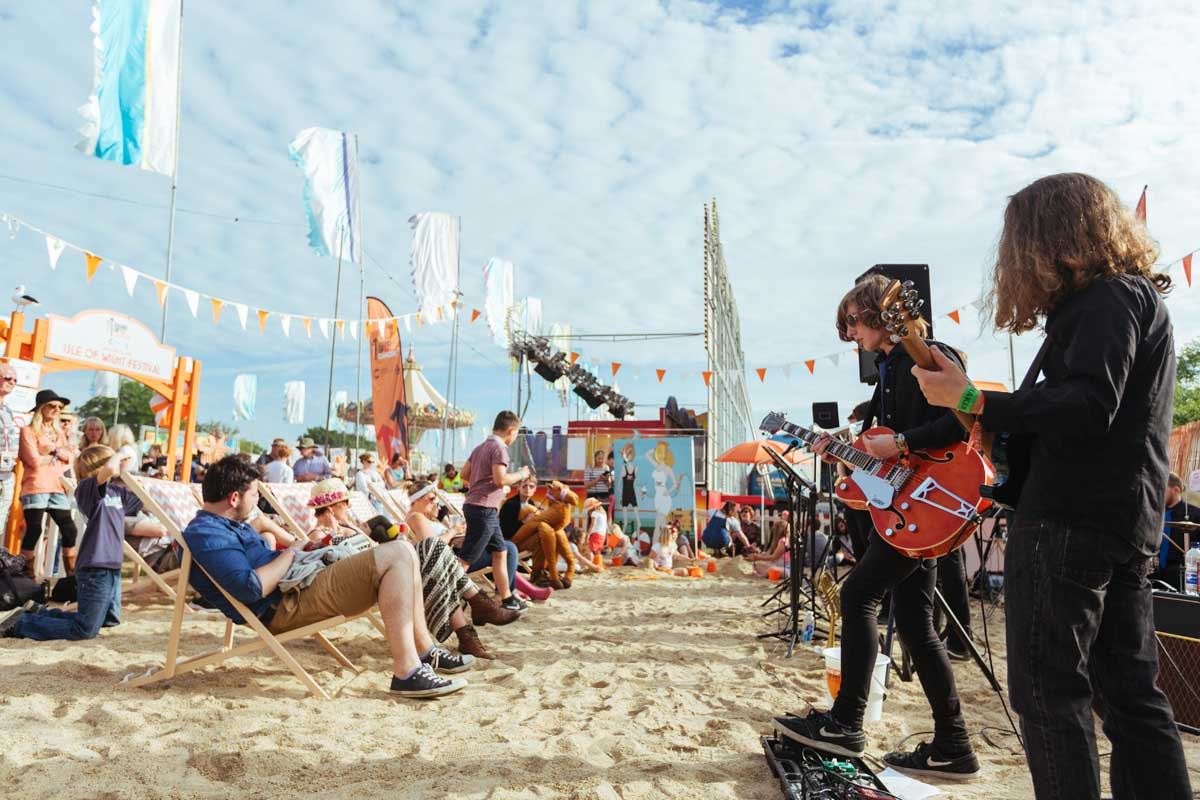 People relaxing on deck chairs in the sand listening to a band performing in front of them