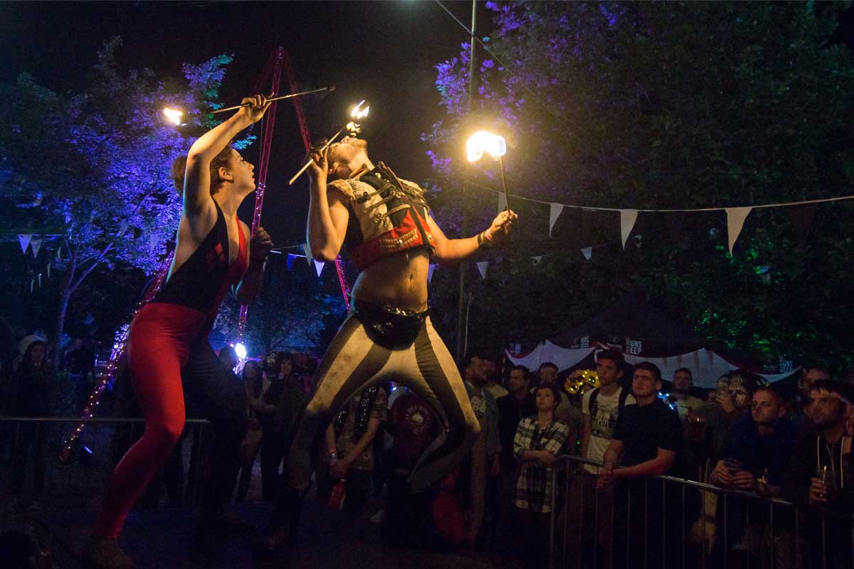 Two circus performers doing a fire-eating act on stage at night