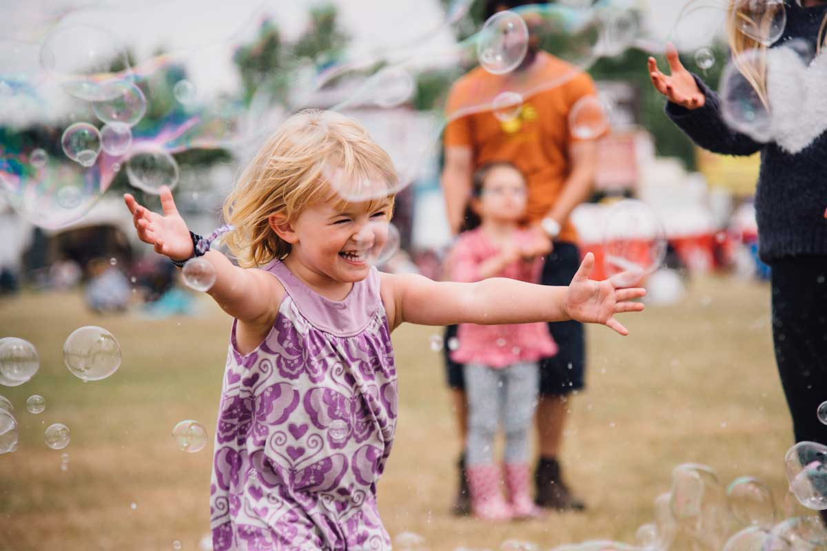 little girl in purple dress racing into flying soap bubbles arms outstretched at Isle of Wight