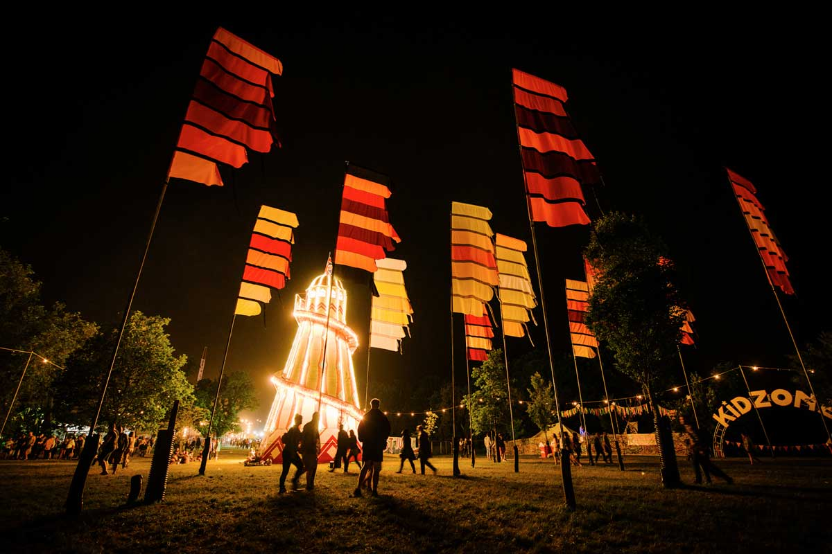 Flags and the lighted up lighthouse at night at the Isle of Wight Festival