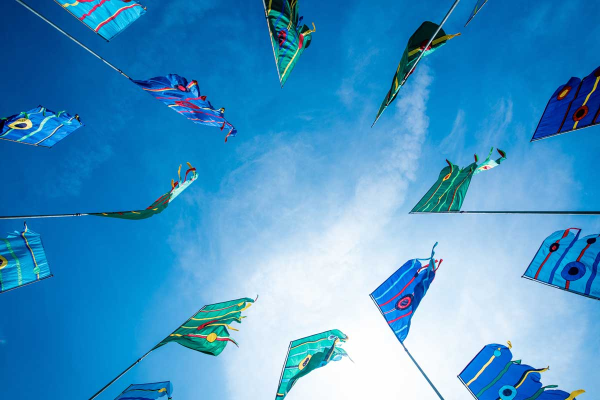 View from below of flags in a circle in the blue sky at the Isle of Wight