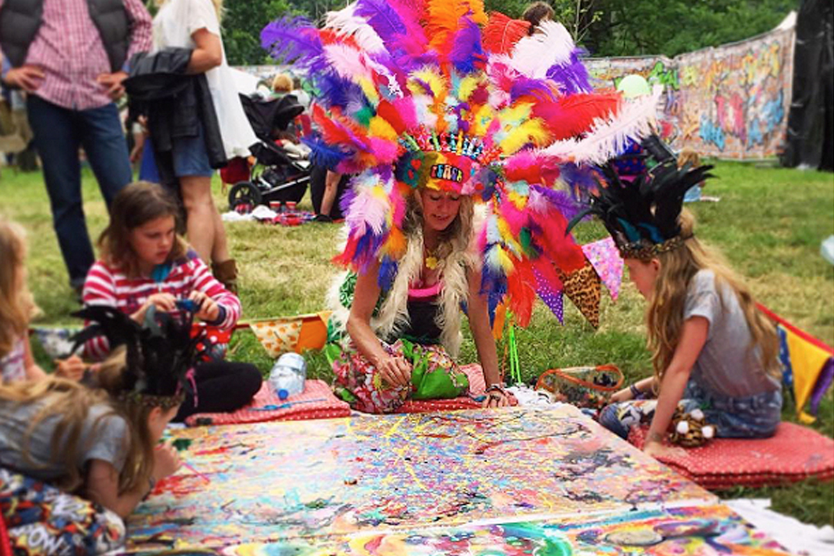 Lady in a huge, multicoloured headdress painting with kids seated on the ground, UK