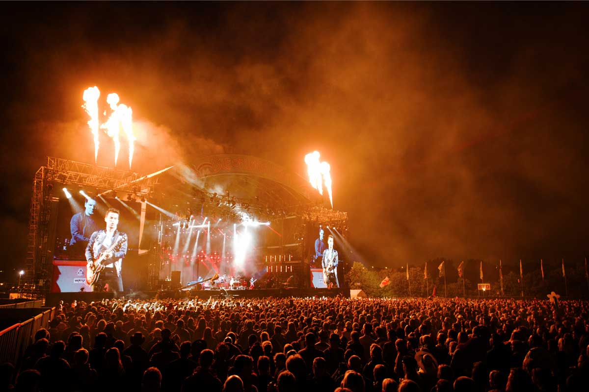 Massive crowd enjoying performance onstage at night at the Isle of Wight Festival