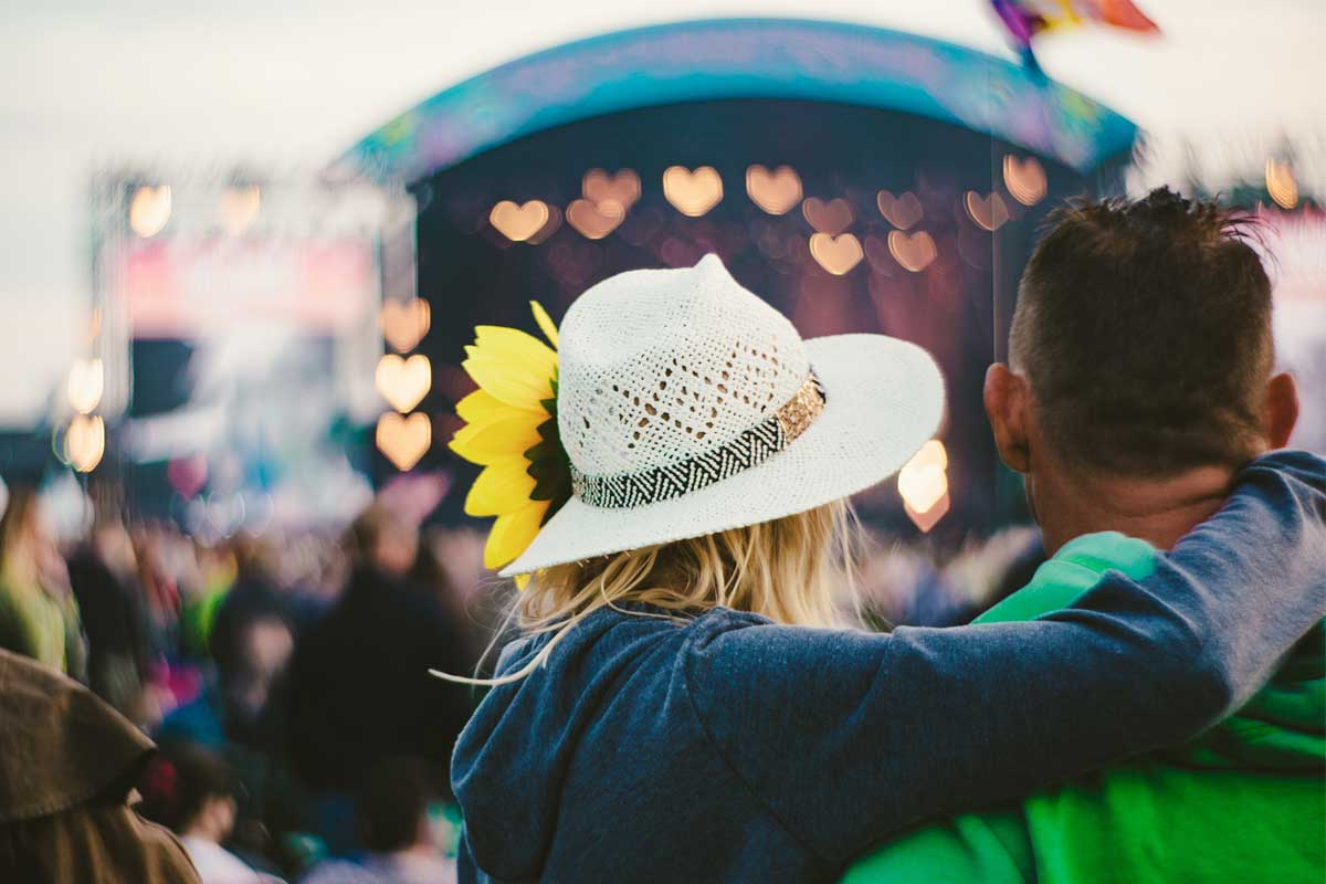 lady in a sunflower adorned hat with arm around a man's shoulders watching stage at Isle of Wight