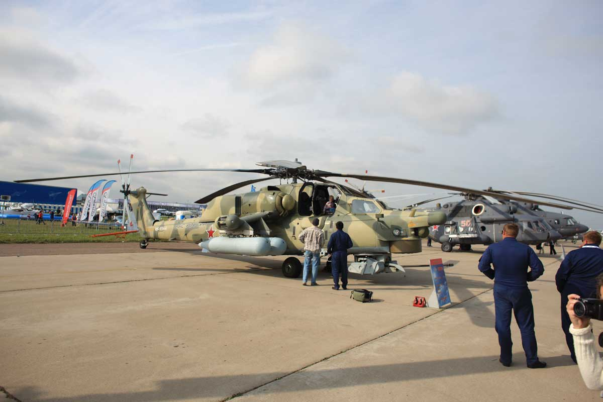 Some people around army helicopters on the tarmac in Russia