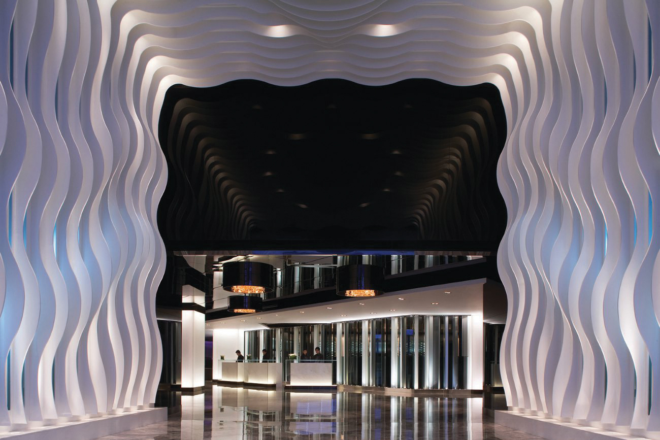 White, wavy strips framing the entryway of a hotel lobby with the reception and glass doors ahead at The Mira, Hong Kong