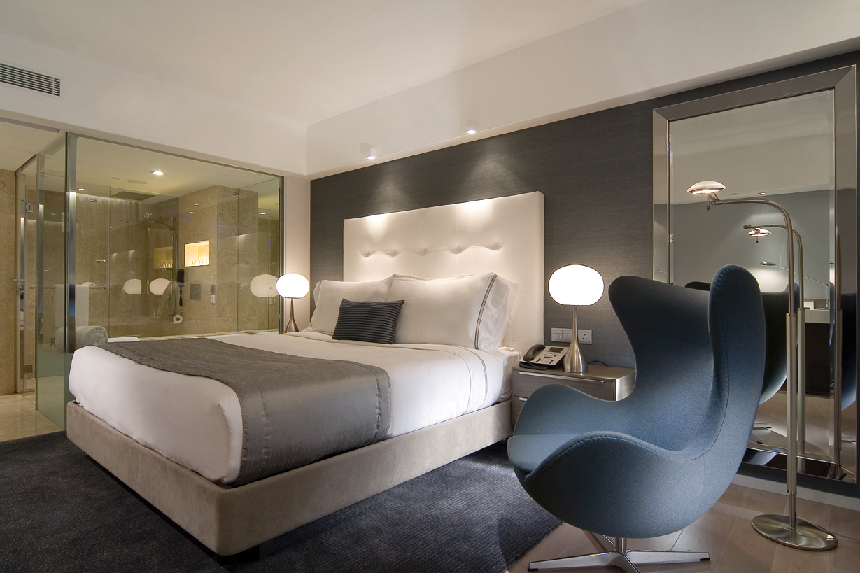 A well-dressed bed with a comfortably upholstered sink-in chair and lamp by it, in a mirror-panelled room, Hong Kong